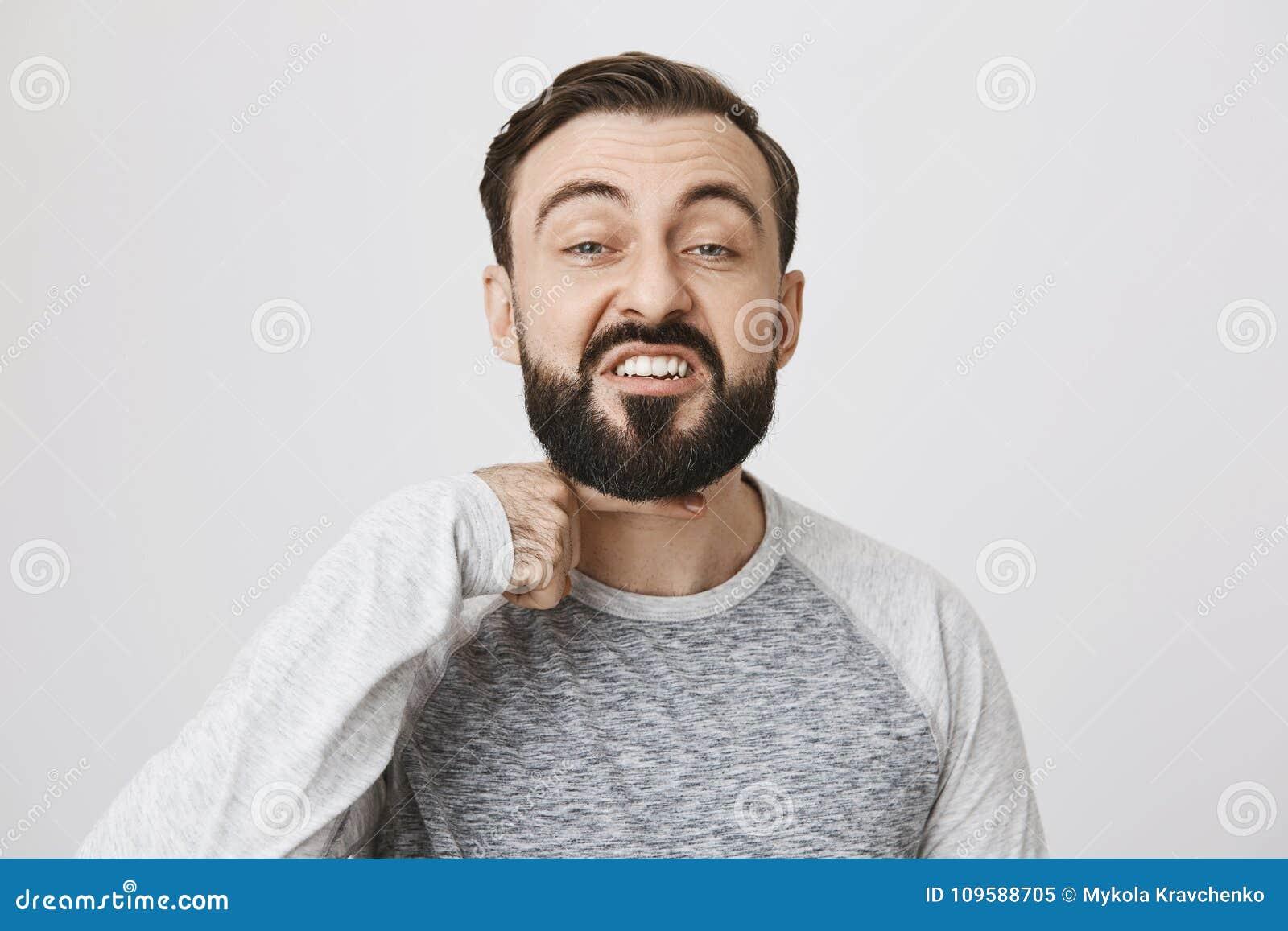 Сердитый бородатый показ парня я отрежу вас возглавляю жест с указательным пальцем над шеей, стоя над серой предпосылкой I