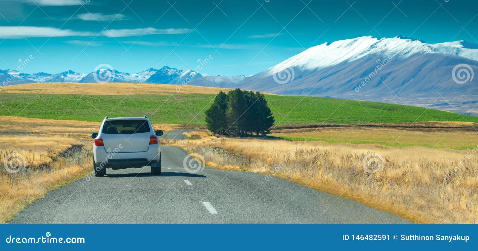 Серебряное вождение автомобиля кроссовера быстро на дороге асфальта сельской местности против голубого неба с белыми облаками Дли