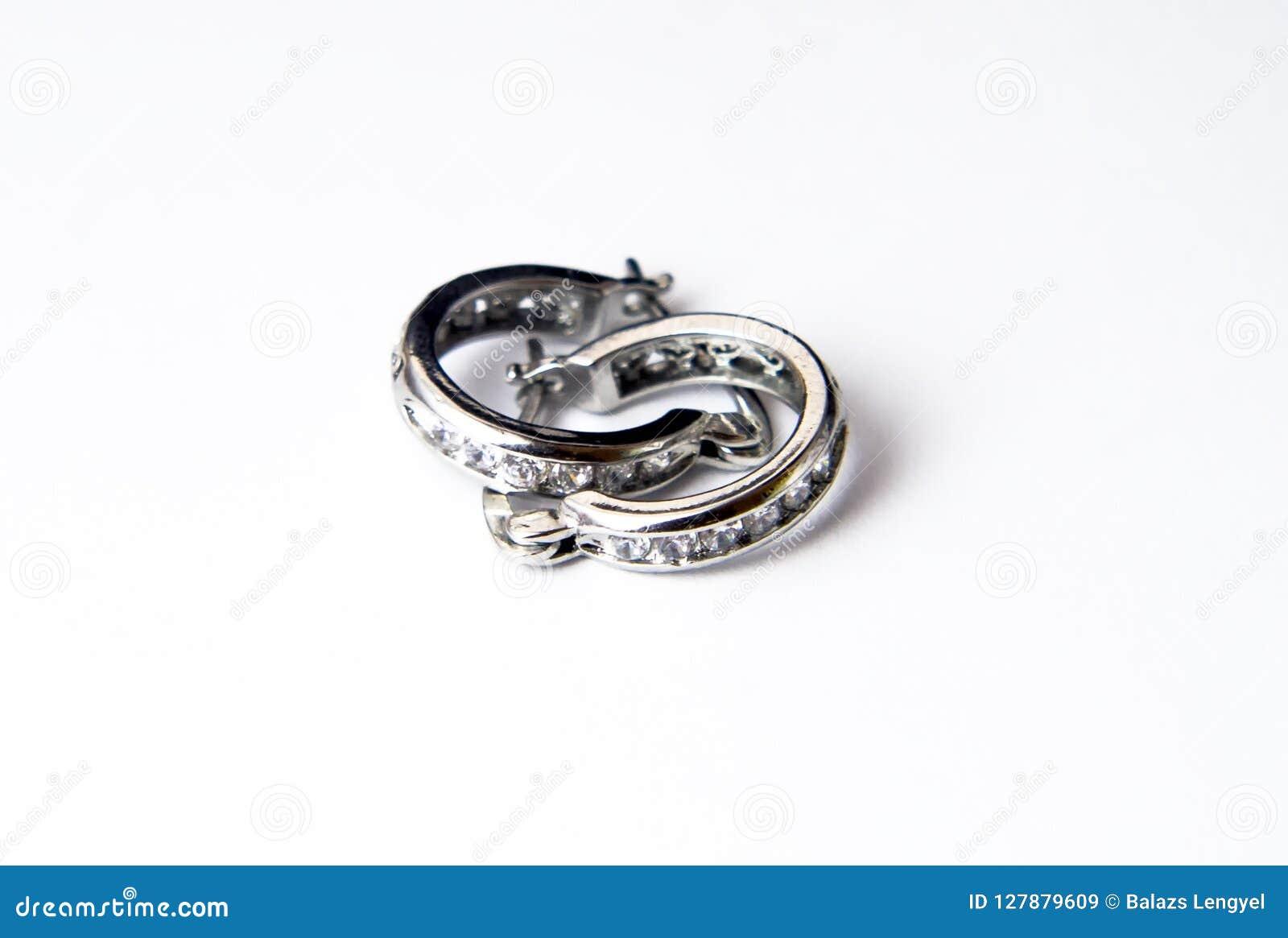 Серебряные серьги изолированные над белой предпосылкой Взгляд сверху, плоский l