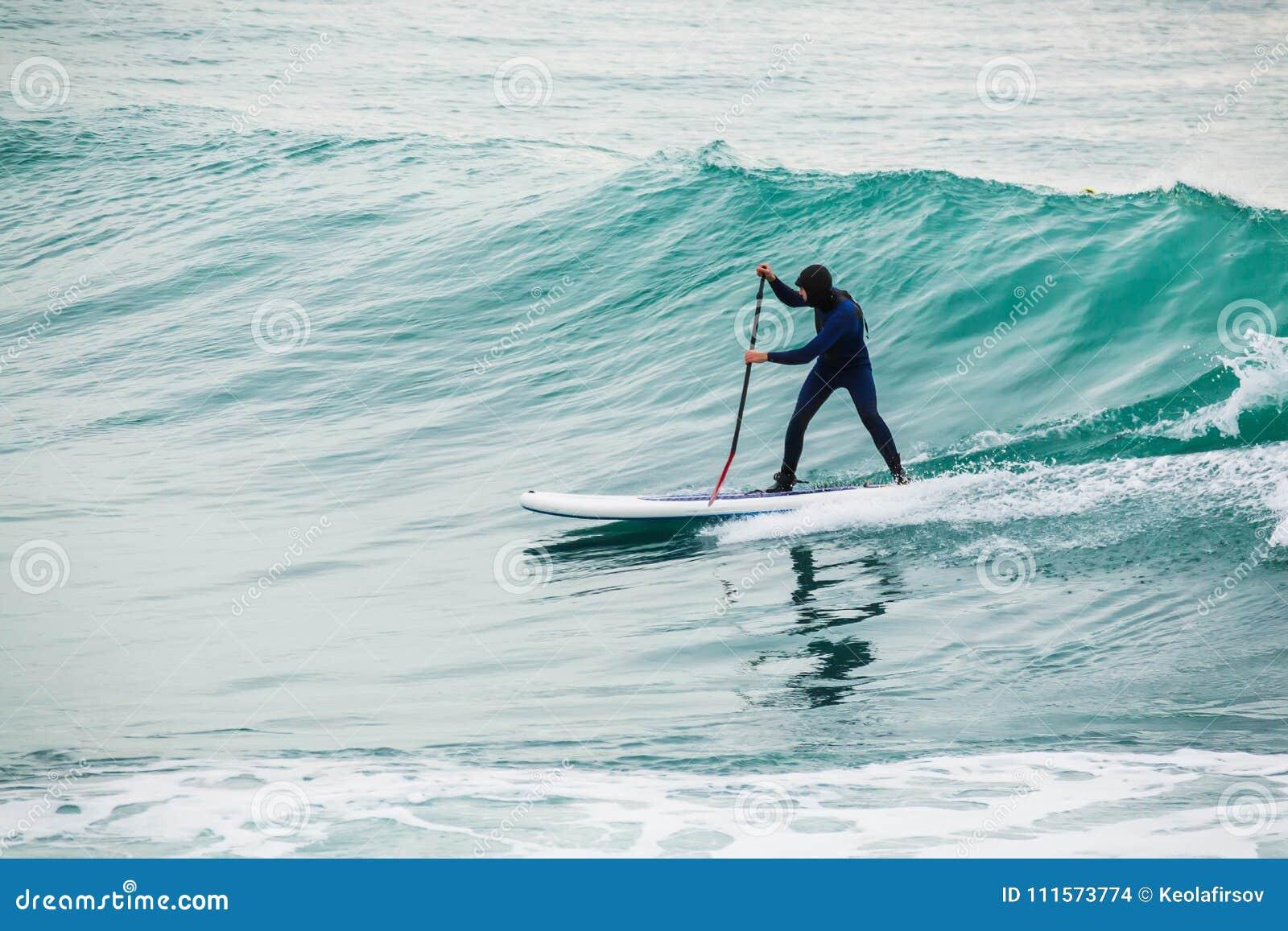 Серфер дальше стоит вверх доска затвора на голубой волне Зима стоит вверх затвор занимаясь серфингом в океане