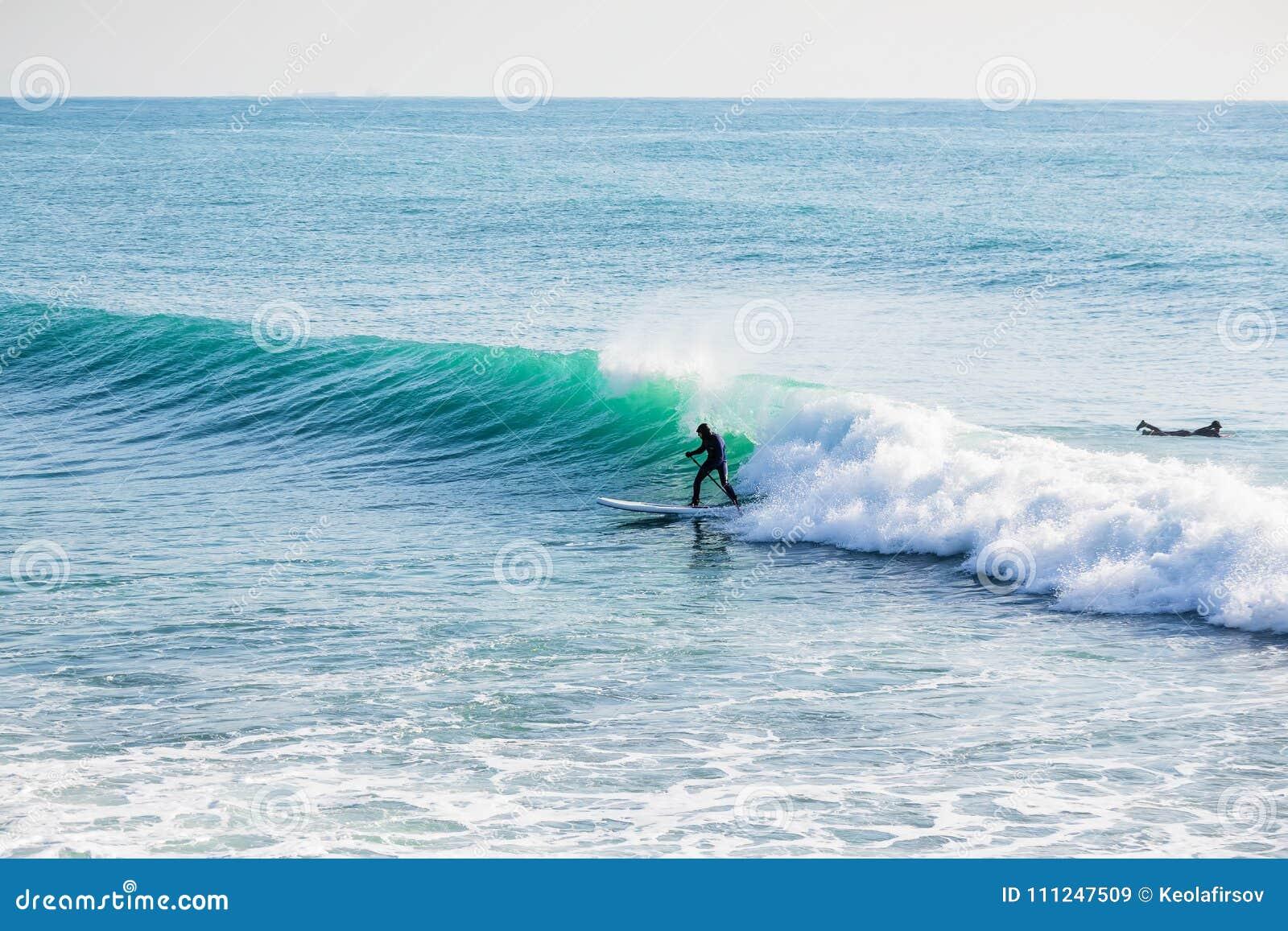 Серфер дальше стоит вверх доска затвора на голубой волне Зима занимаясь серфингом в океане