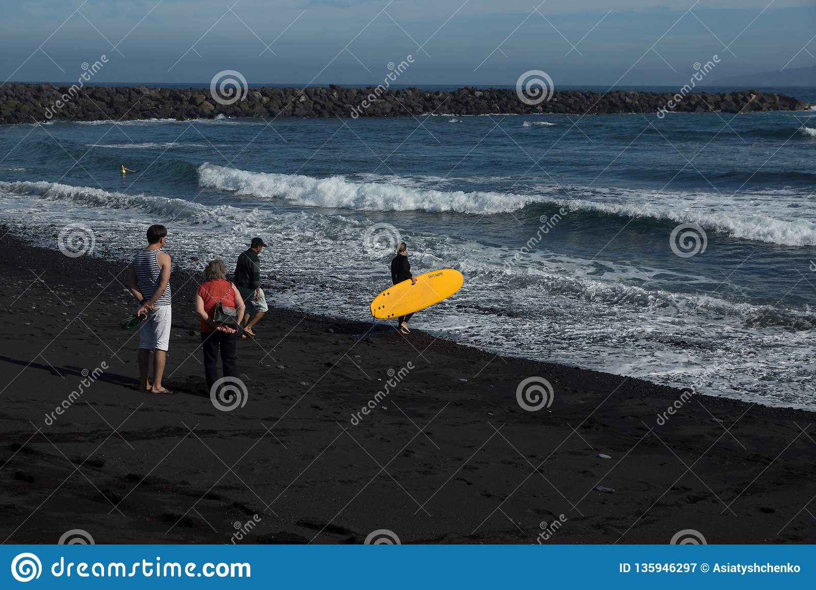 Серфер девушки идет к океану