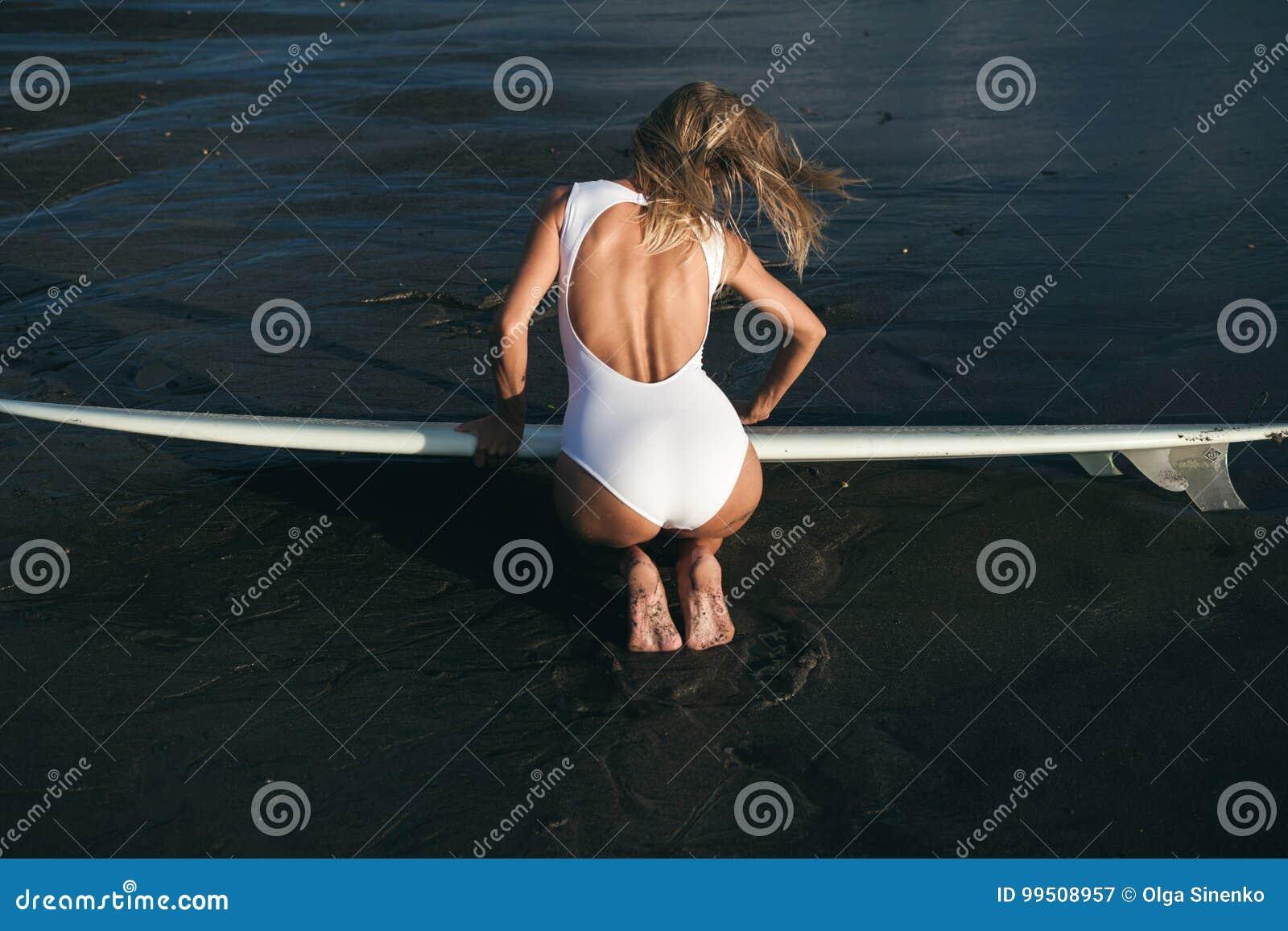 Серфер женщины с доской в руках на пляже