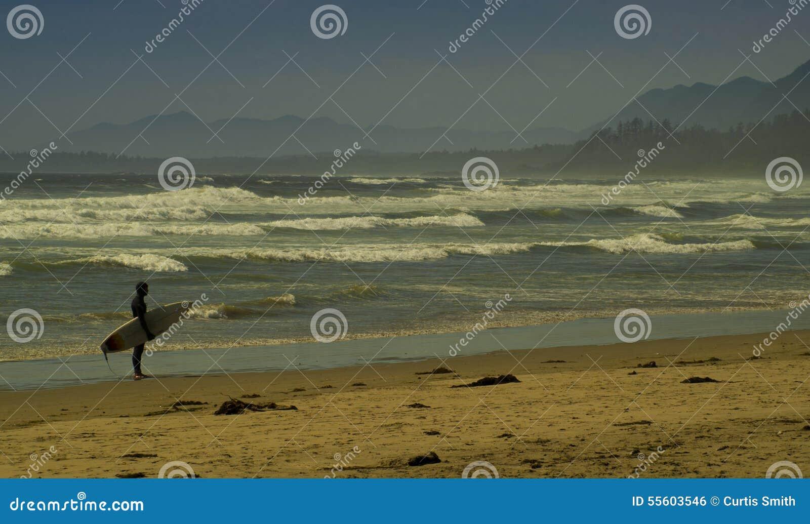Серфер на общественном пляже с волнами и Британской Колумбией Tofino гор