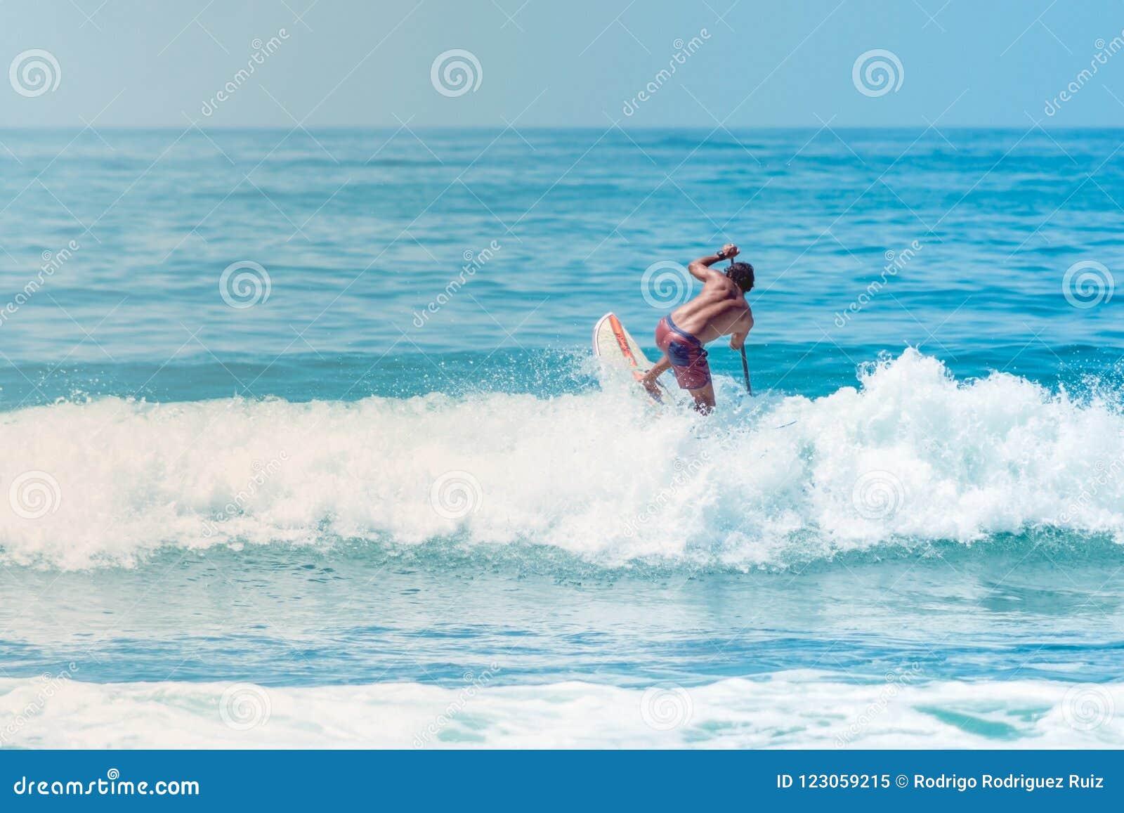 Серфер скача волна на пляж Sayulita Наярита