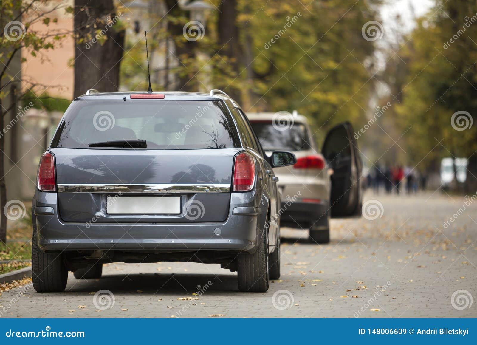 Серый сияющий автомобиль припаркованный в тихом районе на дороге асфальта на запачканной предпосылке bokeh на яркий солнечный ден