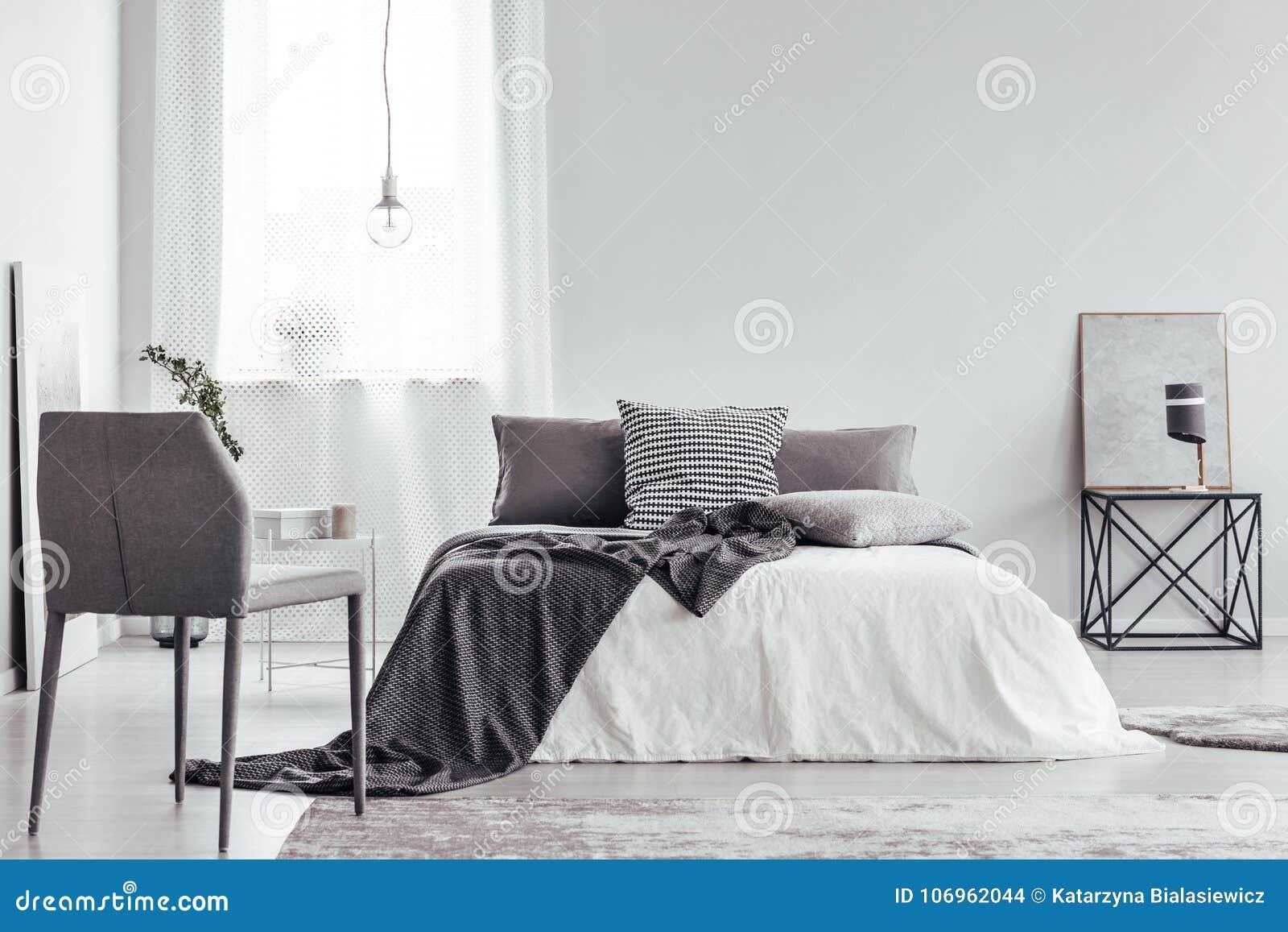 Серый стул в белой спальне