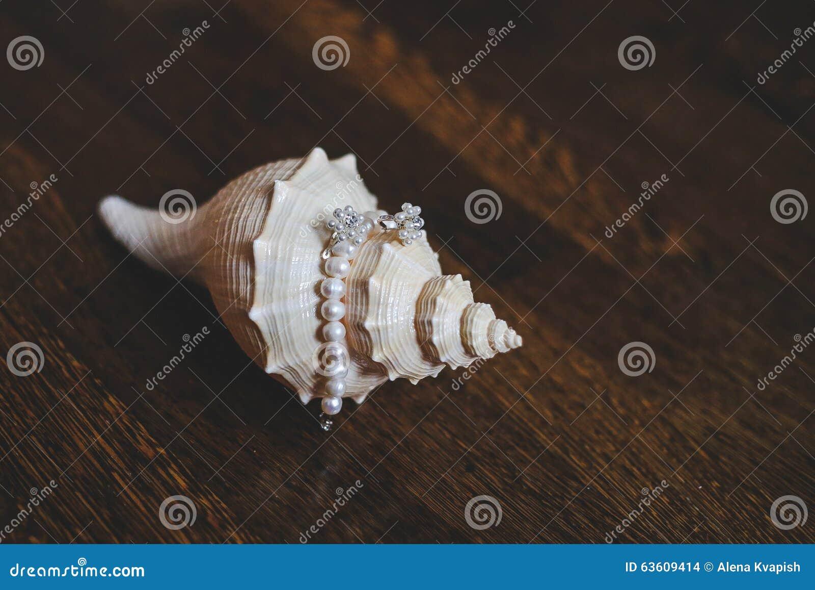 Серьги и браслет жемчугов лежат на раковине