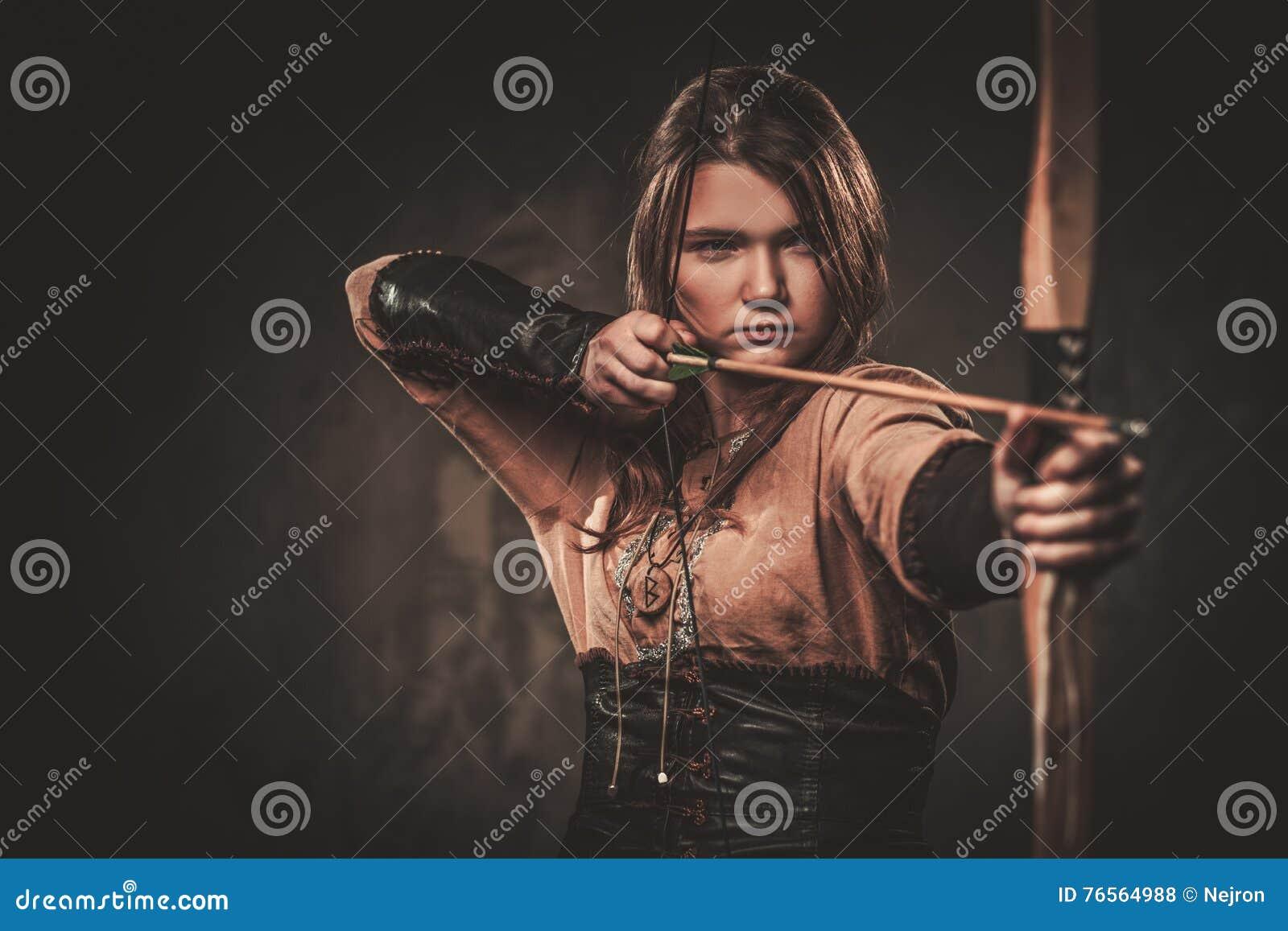Серьезная женщина Викинга с луком и стрелы в традиционном ратнике одевает, представляющ на темной предпосылке