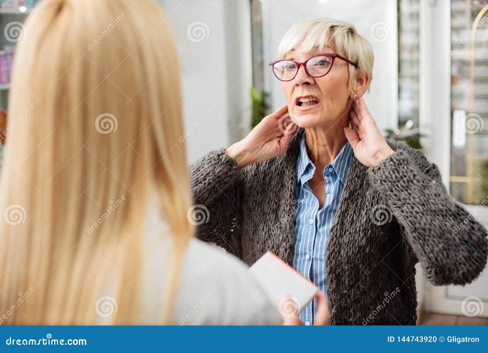 Серьезная старшая женщина с проблемами боли или тиреоида шеи советуя
