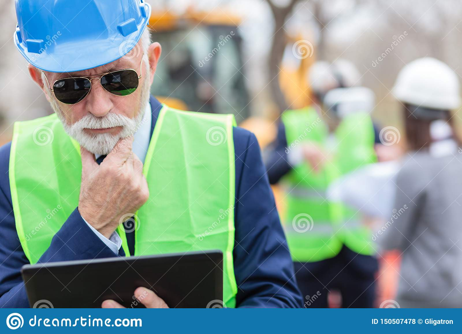 Серьезные, потревоженные, старшиеся серые с волосами инженер или бизнесмен работая на планшете на строительной площадке
