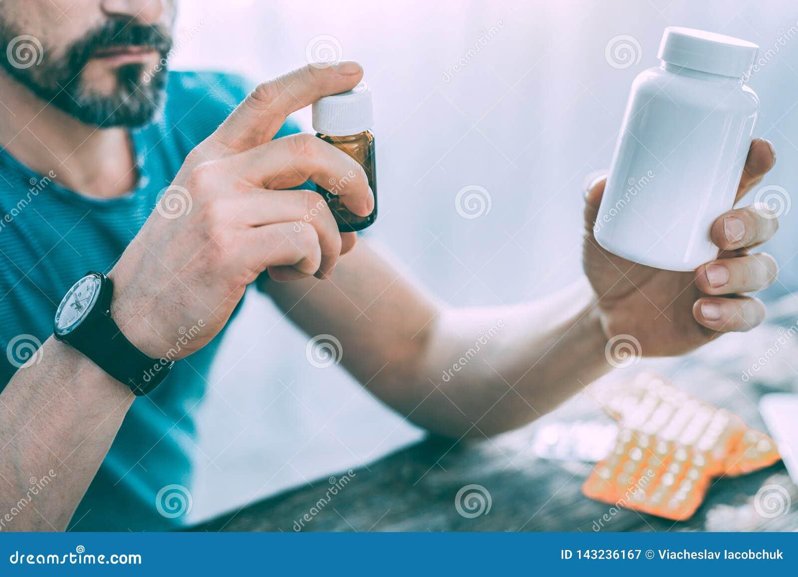 Серьезный больной бородатый человек выбирая некоторые таблетки