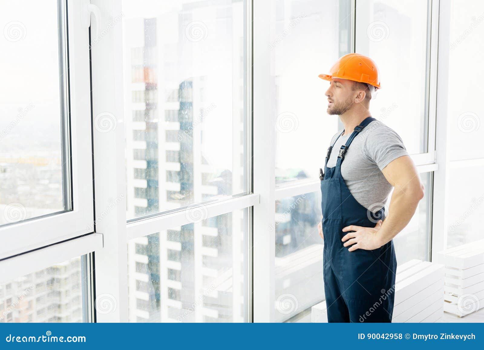 Серьезный инженер по строительству и монтажу стоя близко окно
