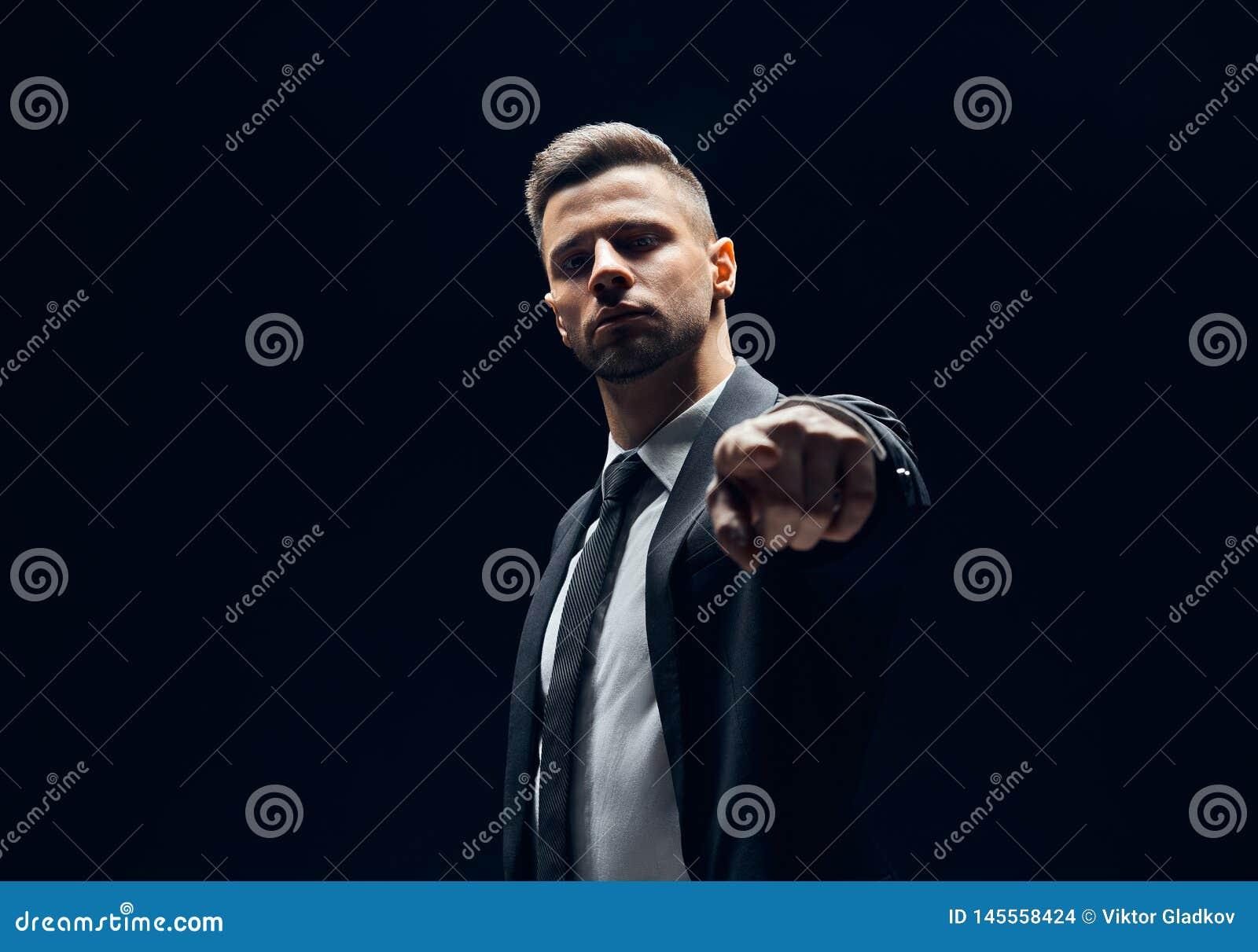 Серьезный красивый человек в черном костюме указывая его палец на вас и камера изолированная на темной предпосылке