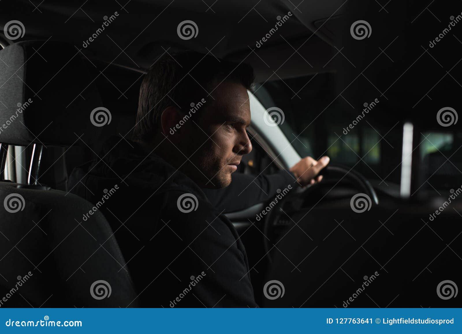 серьезный мужской частный детектив делая наблюдение от