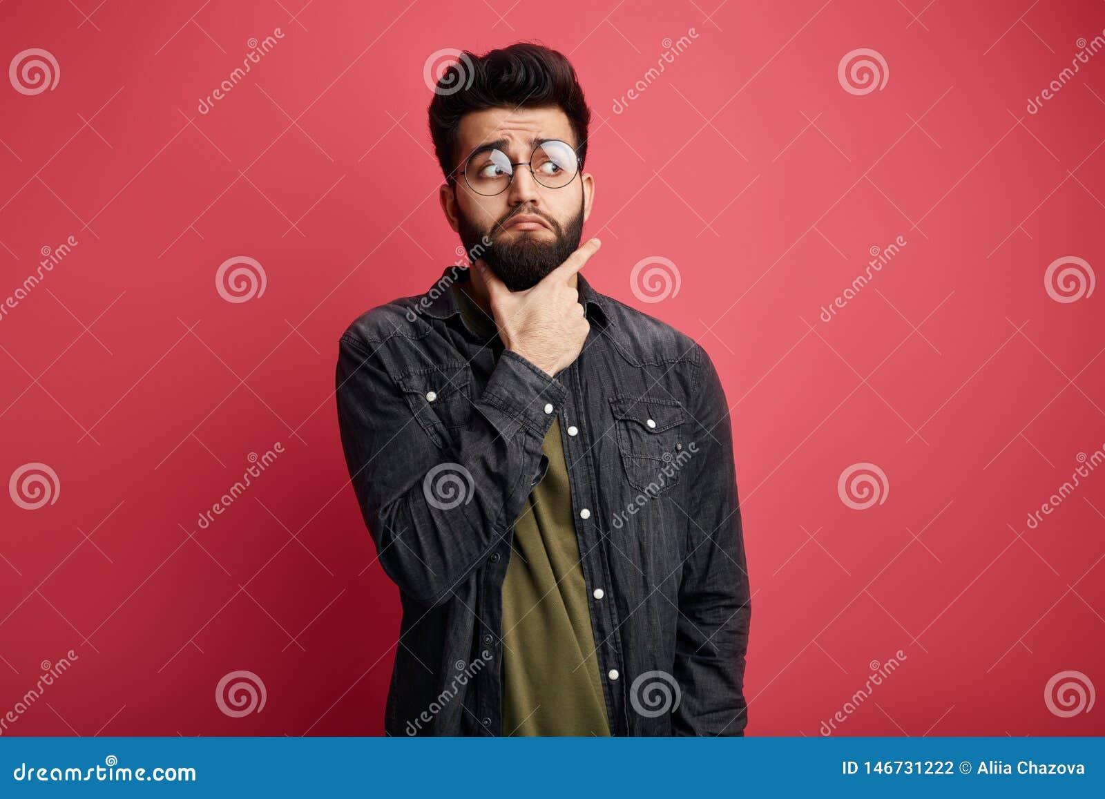 Серьезный привлекательный бородатый стильный человек касаясь подбородку и смотря в сторону на камере