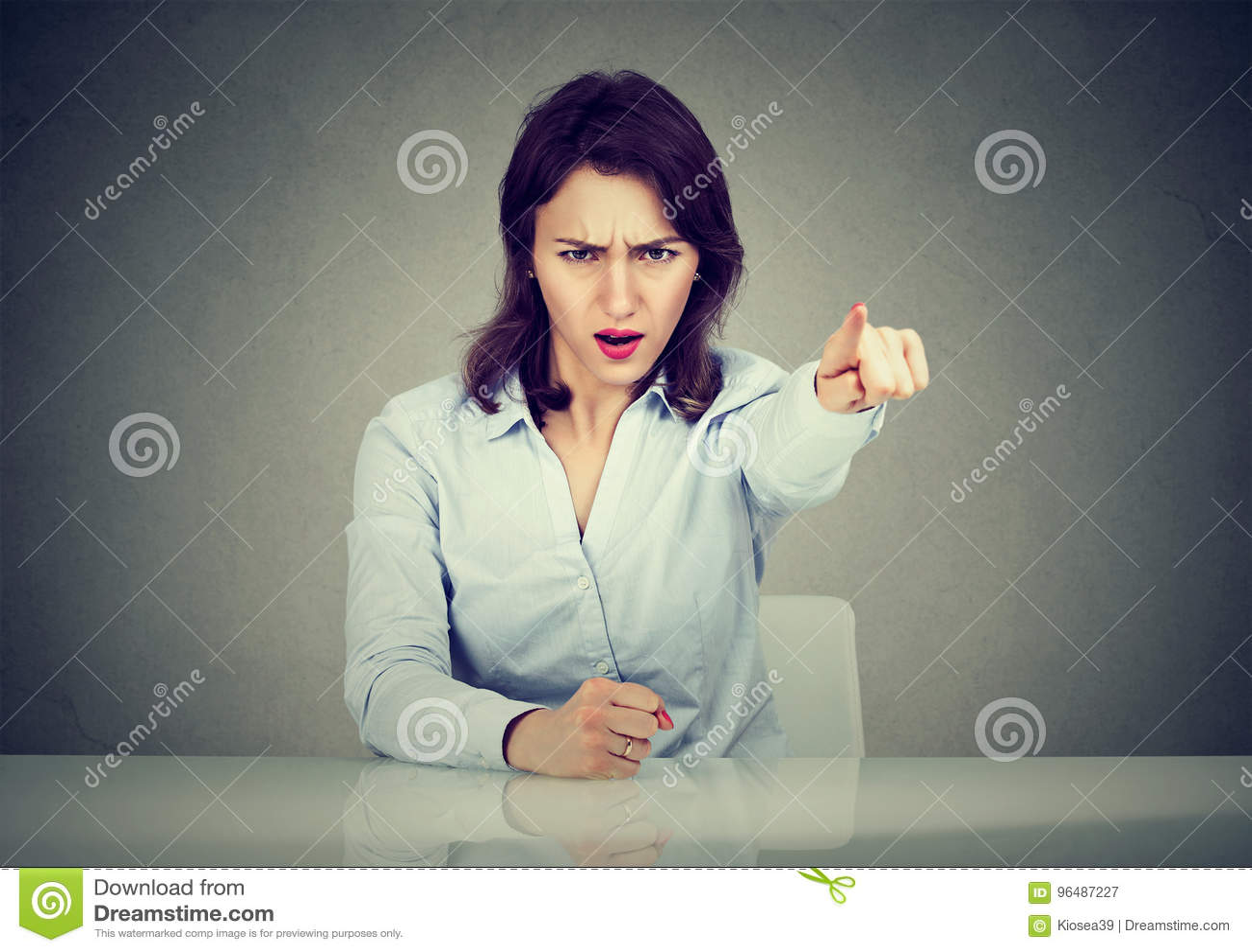 Сердитая бизнес-леди сидя на этап стола кричащий с пальцем, который нужно выйти