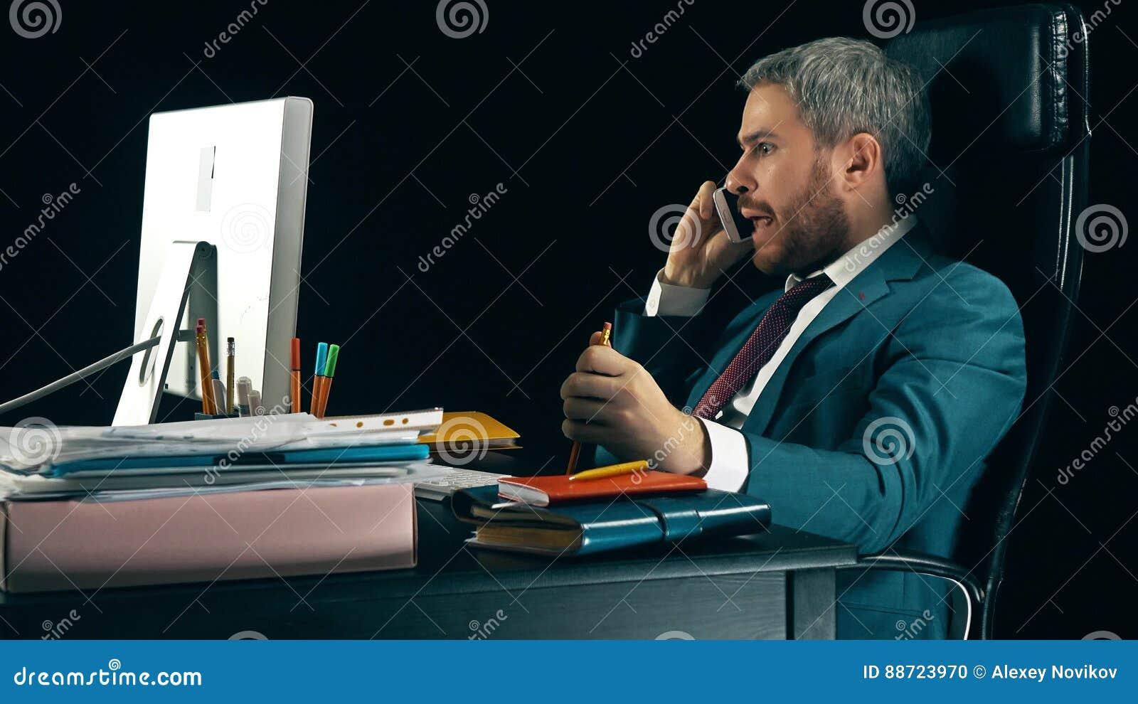 Сердитый бородатый бизнесмен имея эмоциональный напряжённый переговор на его сотовом телефоне Черная предпосылка