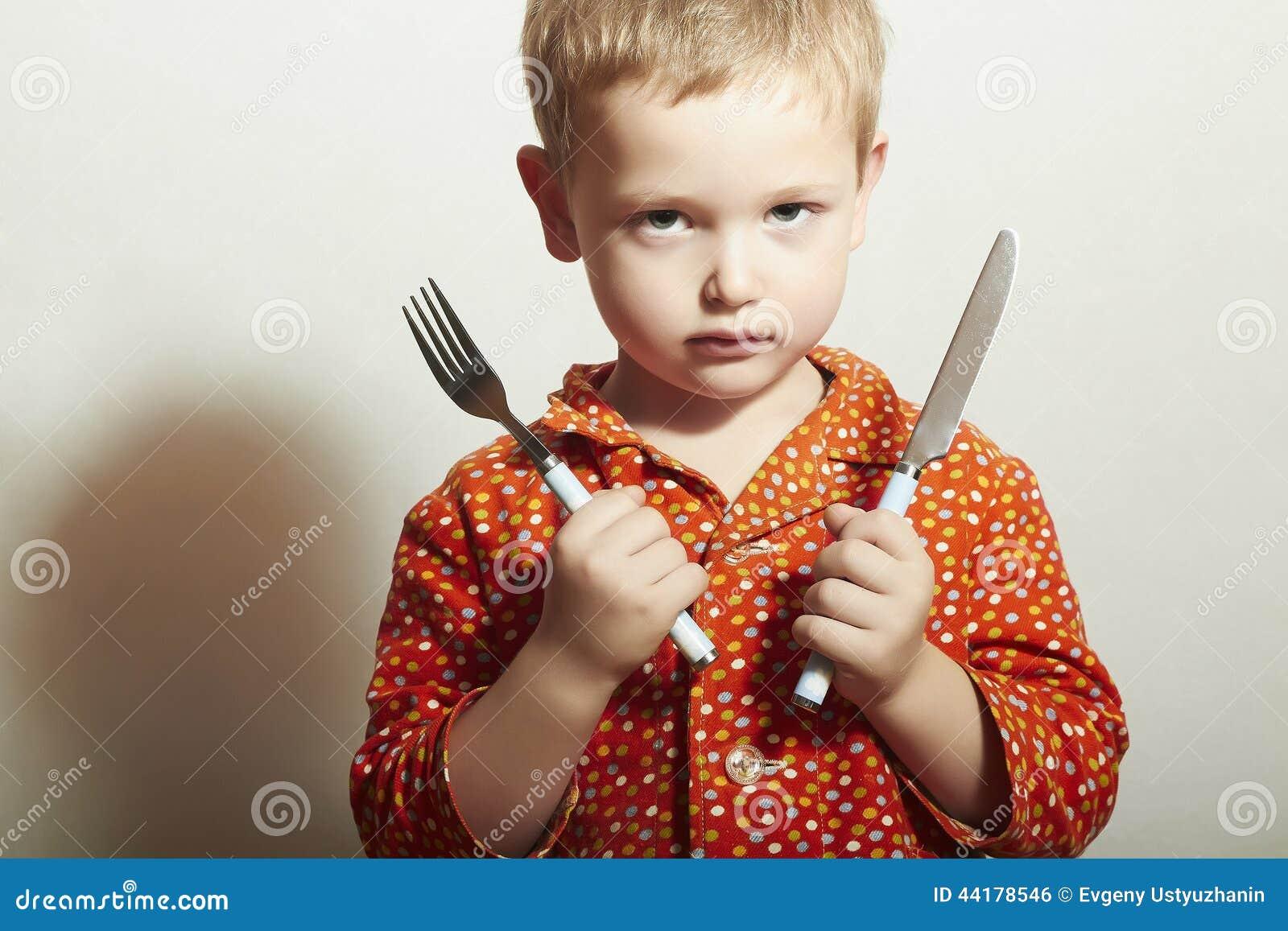 Сердитый ребенок голодный мальчик с вилкой и ножом Питание съешьте для того чтобы хотеть