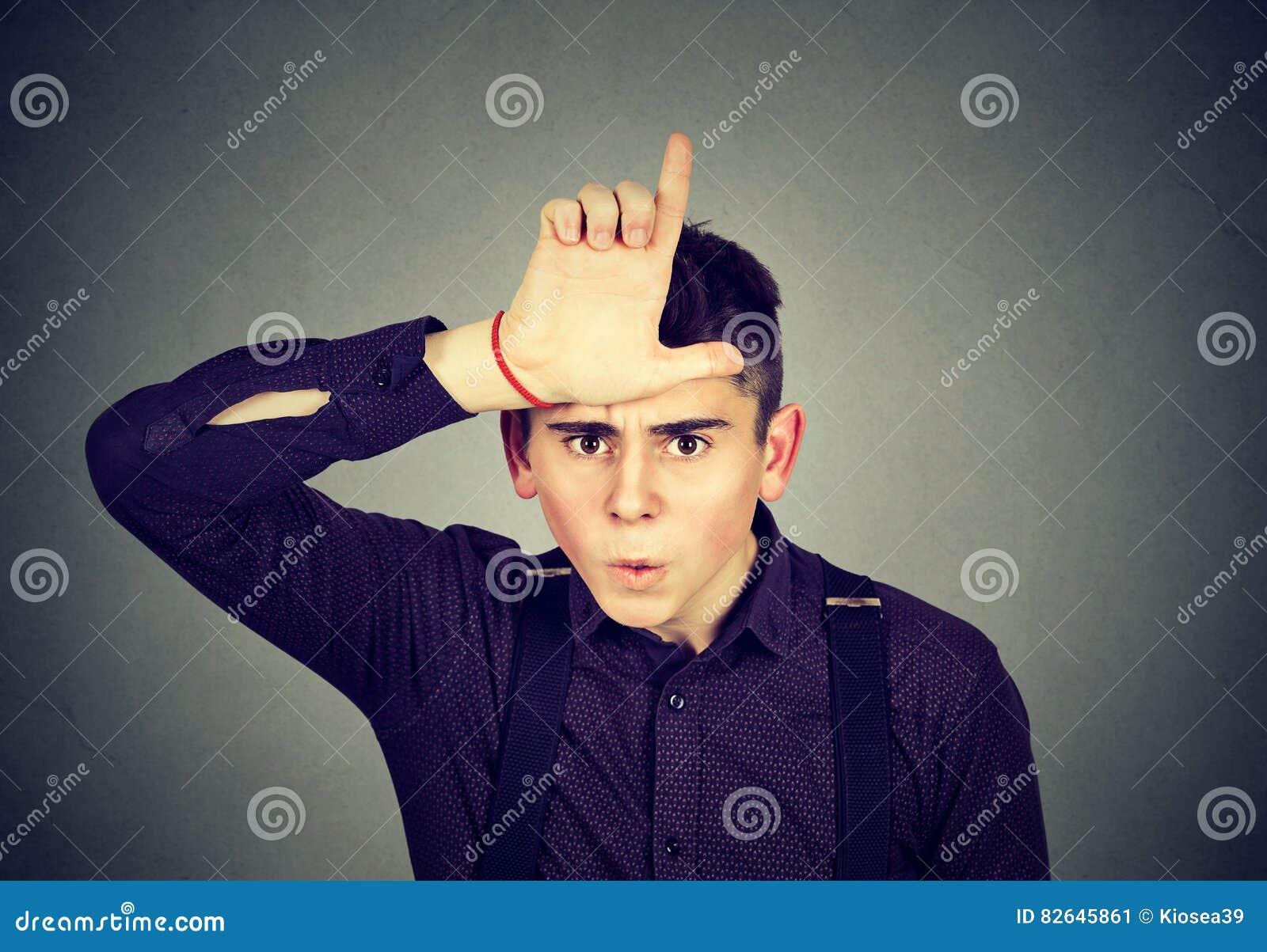 Сердитый человек показывая знак проигравшего смотря с отвращением на камере