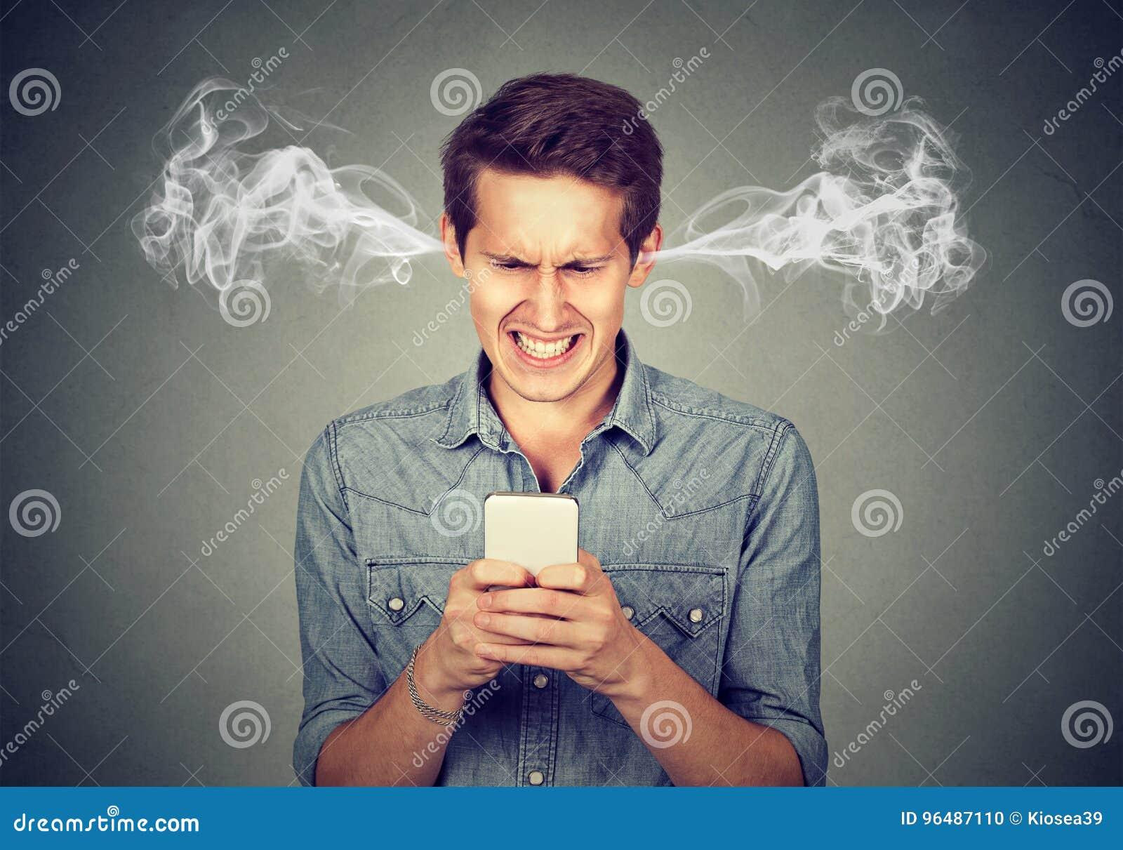 Сердитый человек читая текстовое сообщение на паре smartphone дуя приходя из ушей