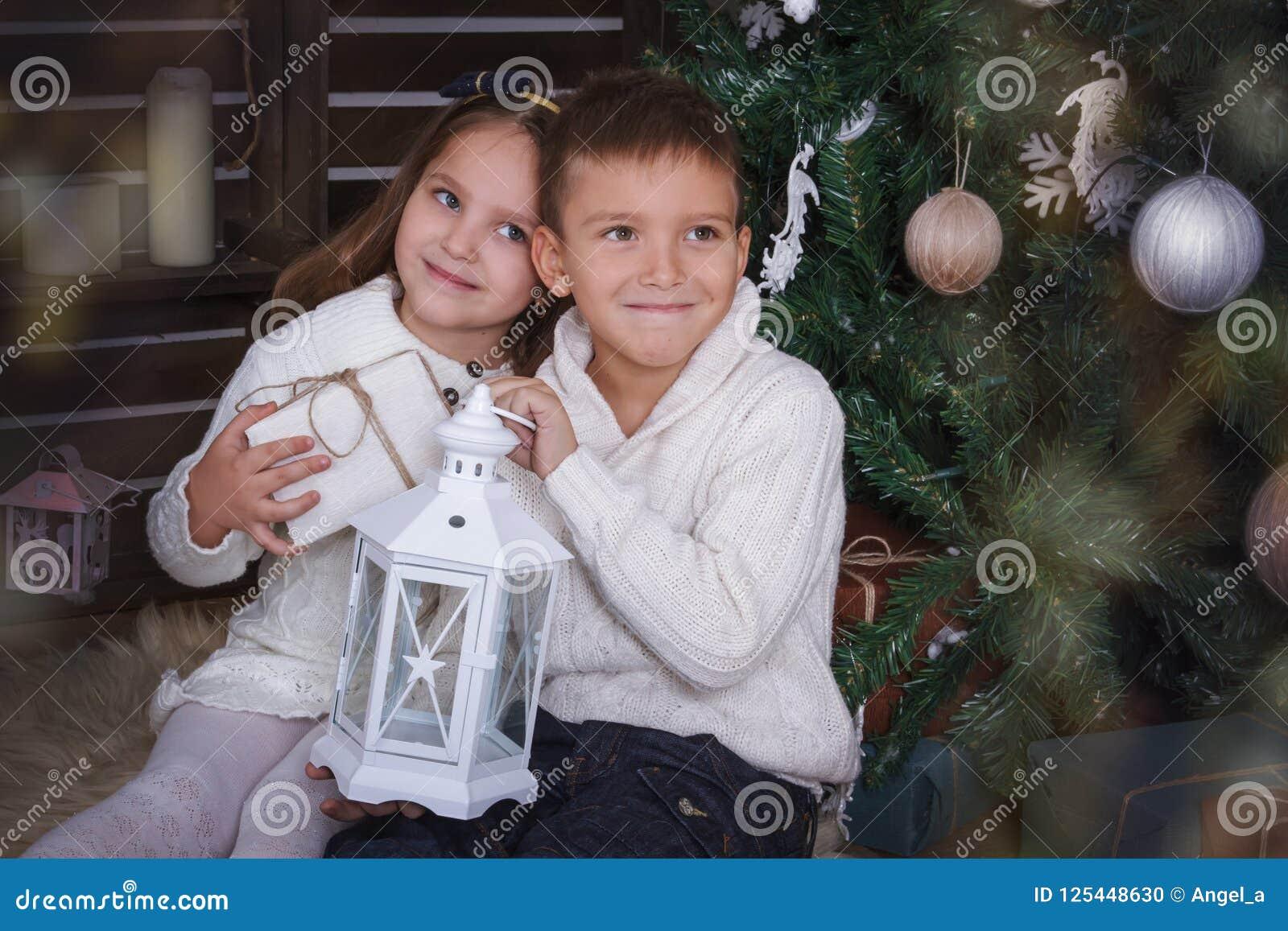 Сестра и брат сидя под рождественской елкой с подарками