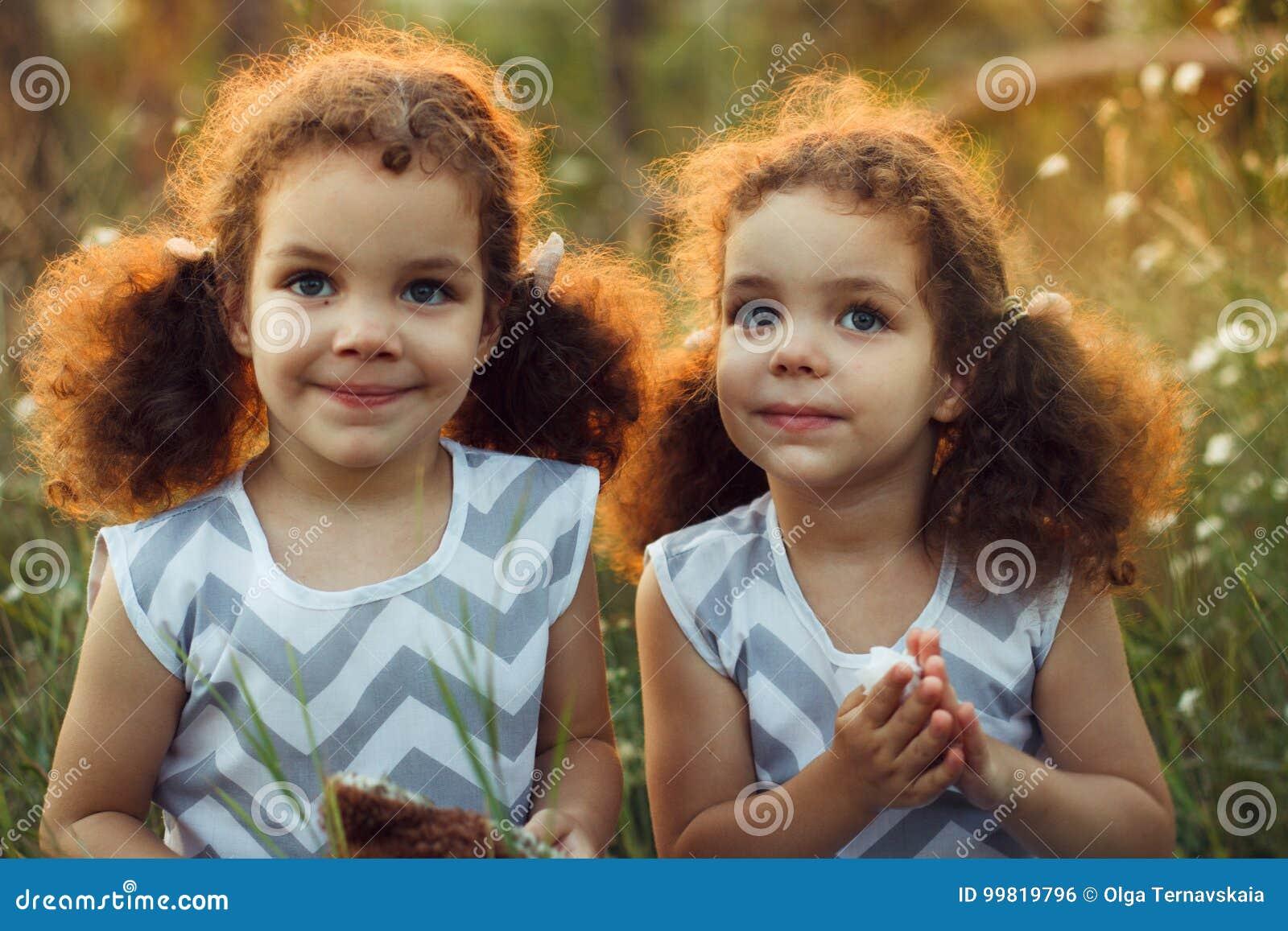 Сестры дублируют малышей целуя и смеясь над в лете outdoors Курчавые милые девушки Приятельство в детстве Теплое sunligh