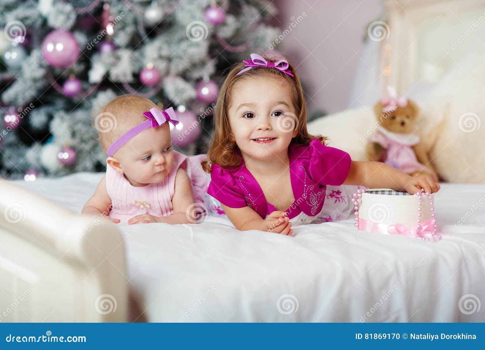 2 сестры дома с рождественской елкой Портрет счастливых украшений девушек детей