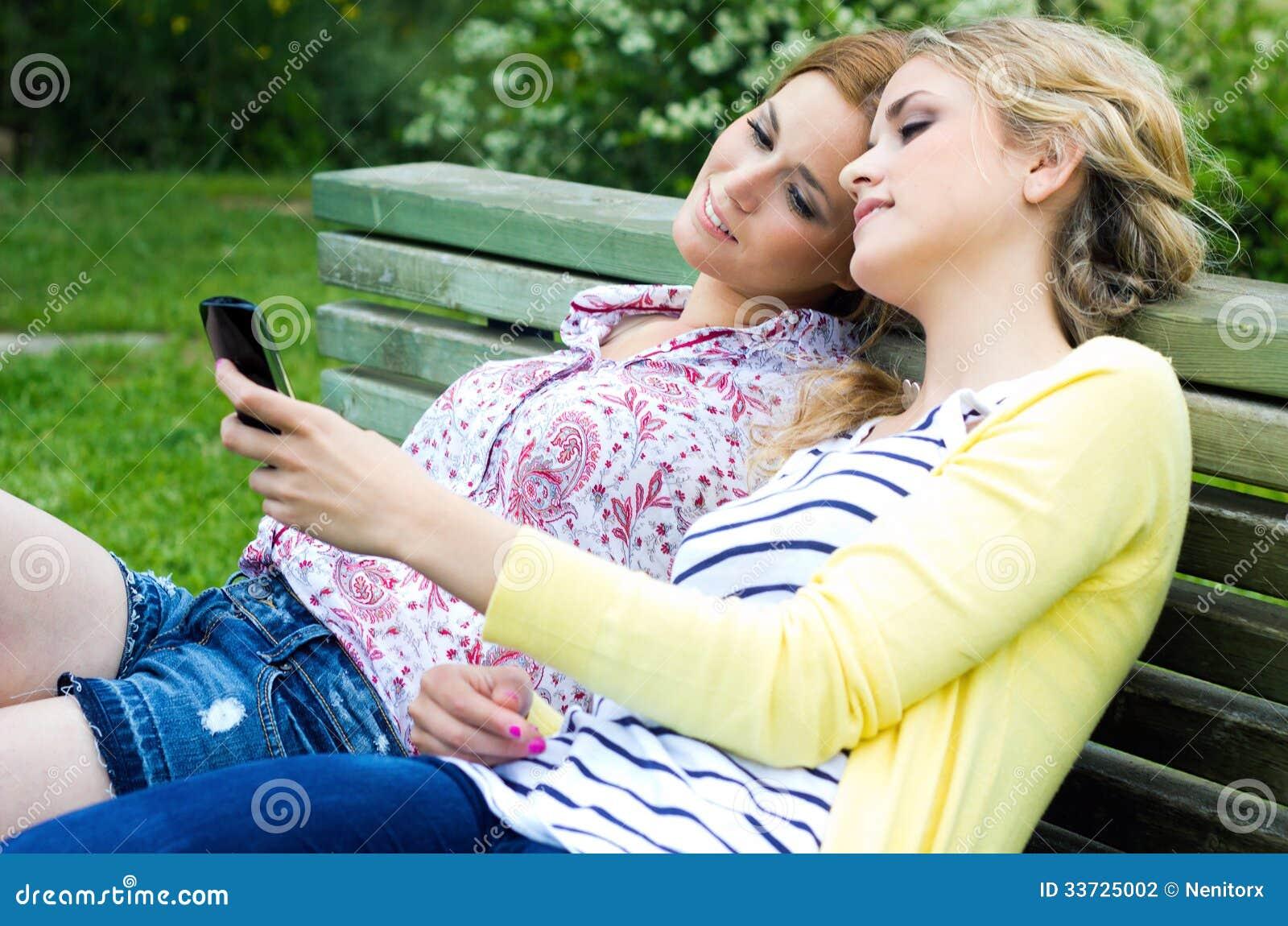 2 сестры с smartphone на парке