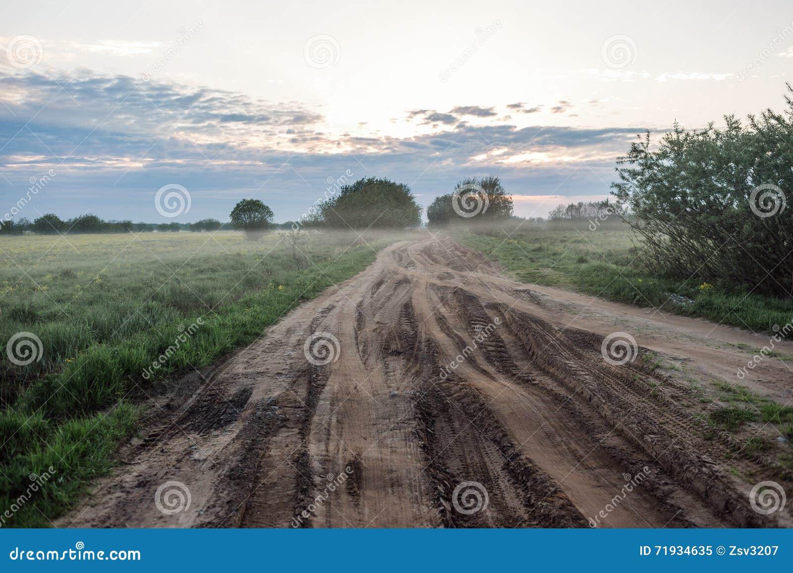 Сельская дорога ландшафта восхода солнца раннего утра в колейностях и тумане