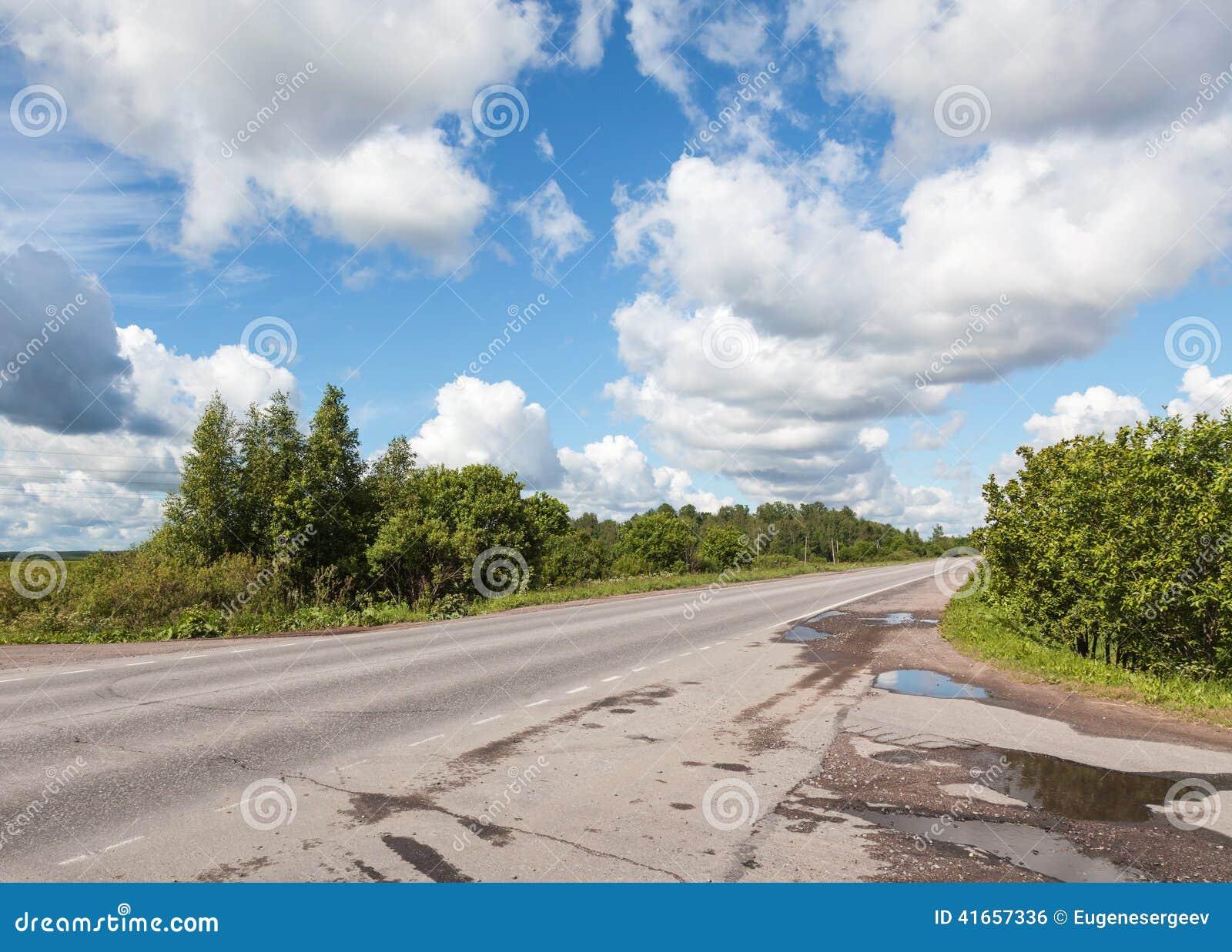 Сельские дорога и облака асфальта на голубом небе