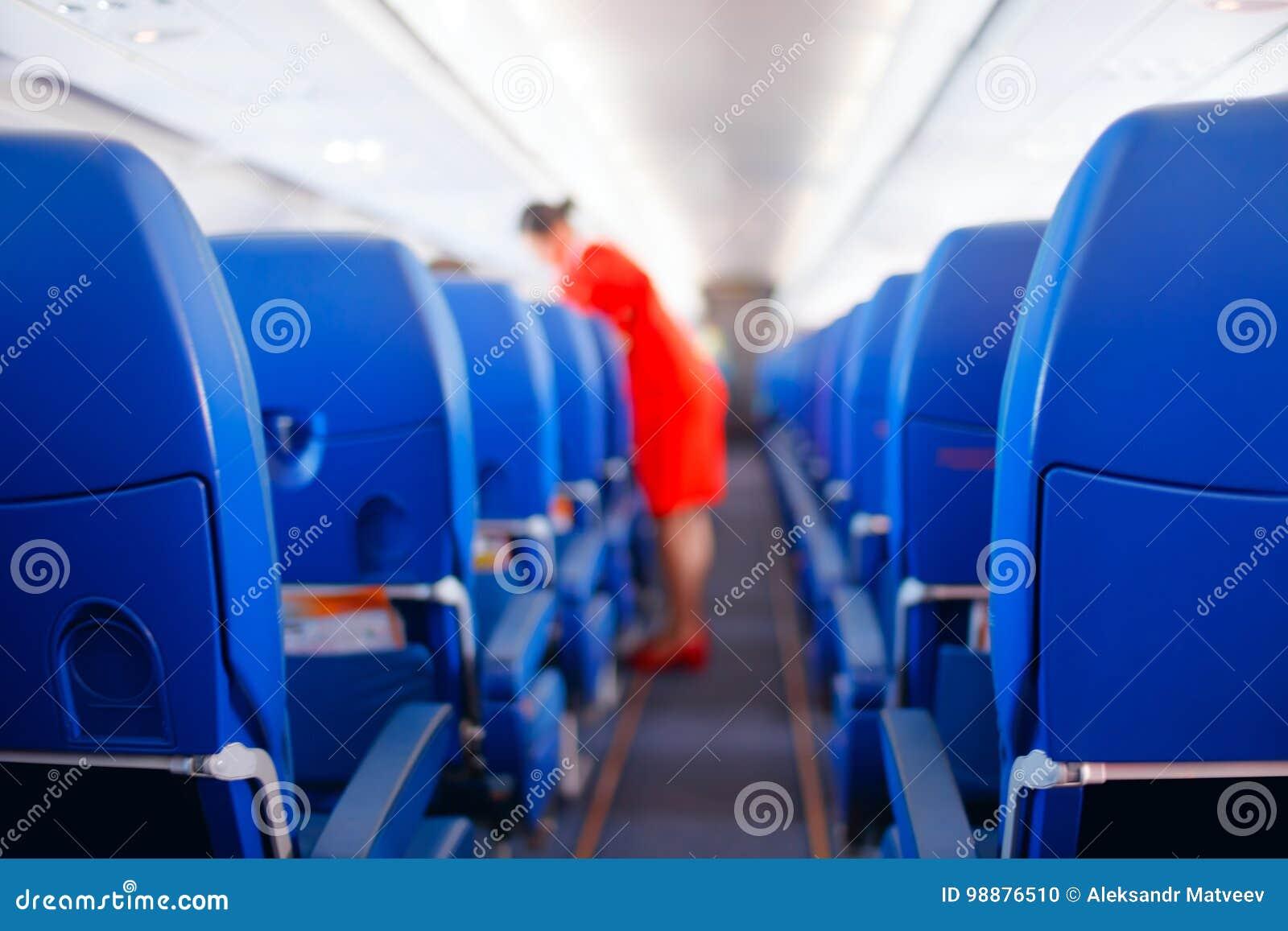 Сиденье пассажира, интерьер самолета при пассажиры сидя на местах и stewardess идя междурядье в предпосылке stewardess s