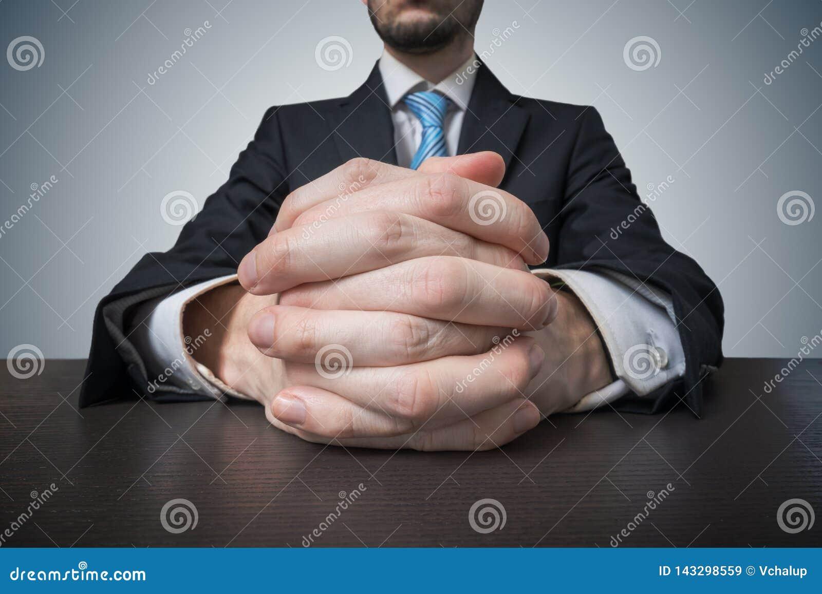 Сидя бизнесмен со сжиманными руками Переговоры и концепция общаться
