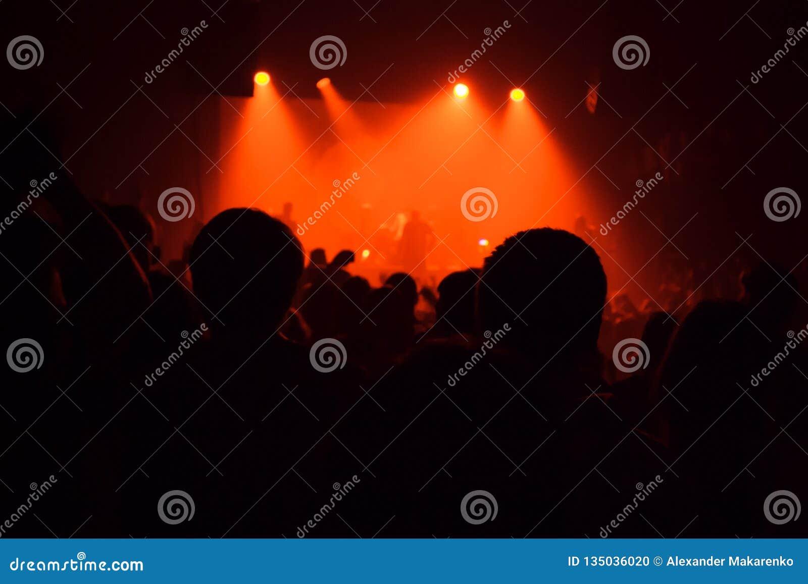 Силуэты аудитории толпятся в шоу утеса большого концертного зала наблюдая