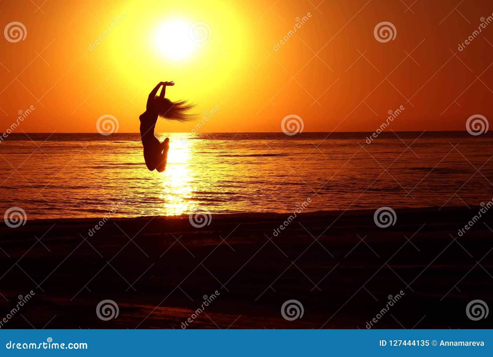 Силуэты девушки скача на заход солнца