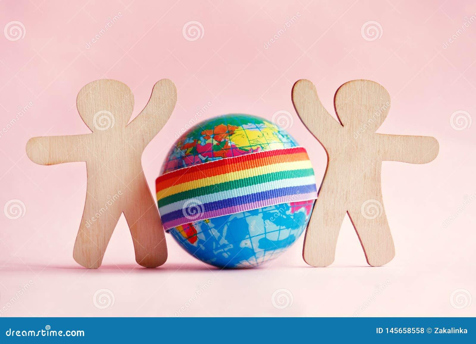 Силуэты мини игрушки деревянные людей и глобуса с лентой радуги LGBT на розовой предпосылке