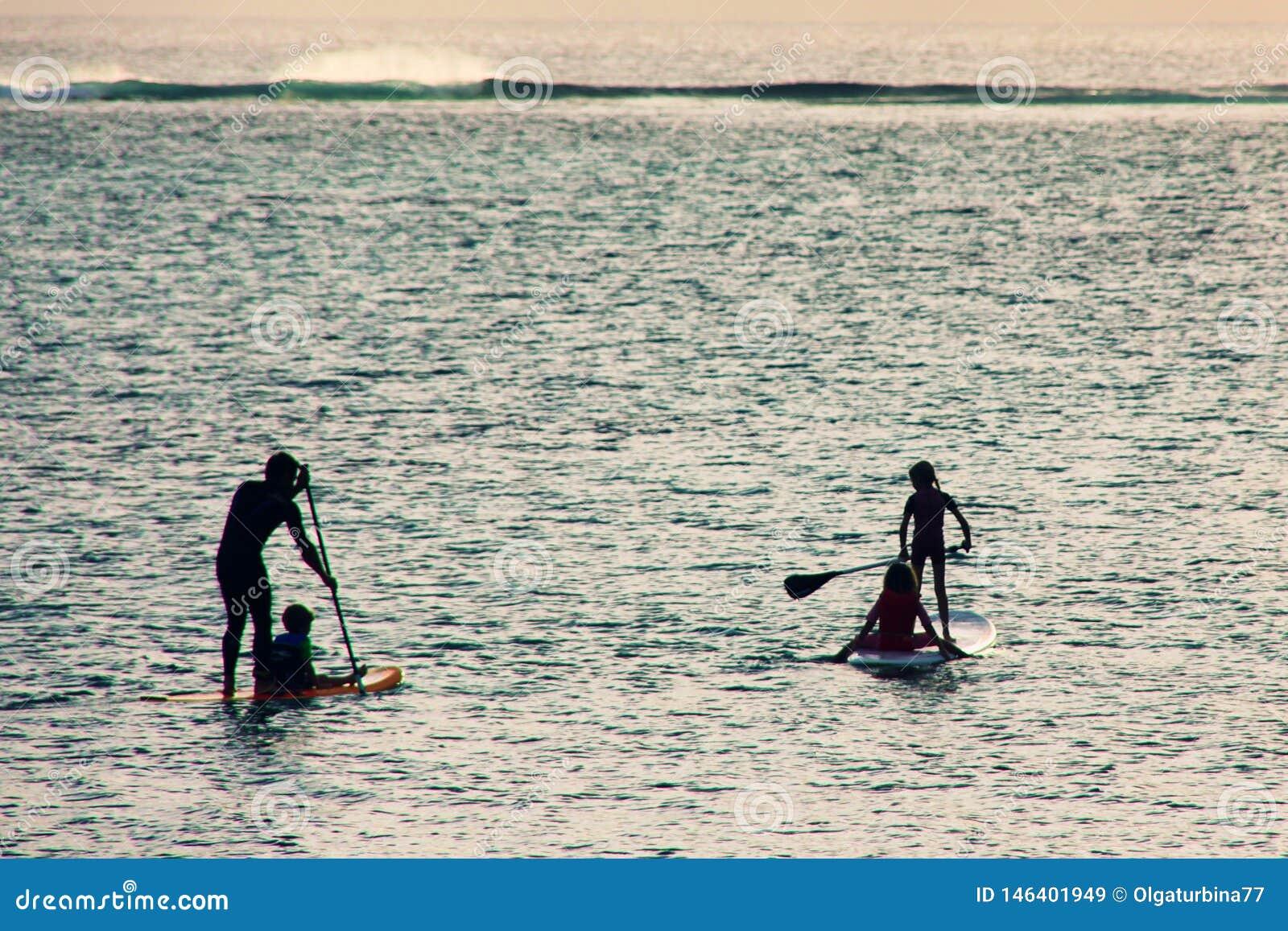 Силуэты семьи на заходе солнца на океане Familysupping