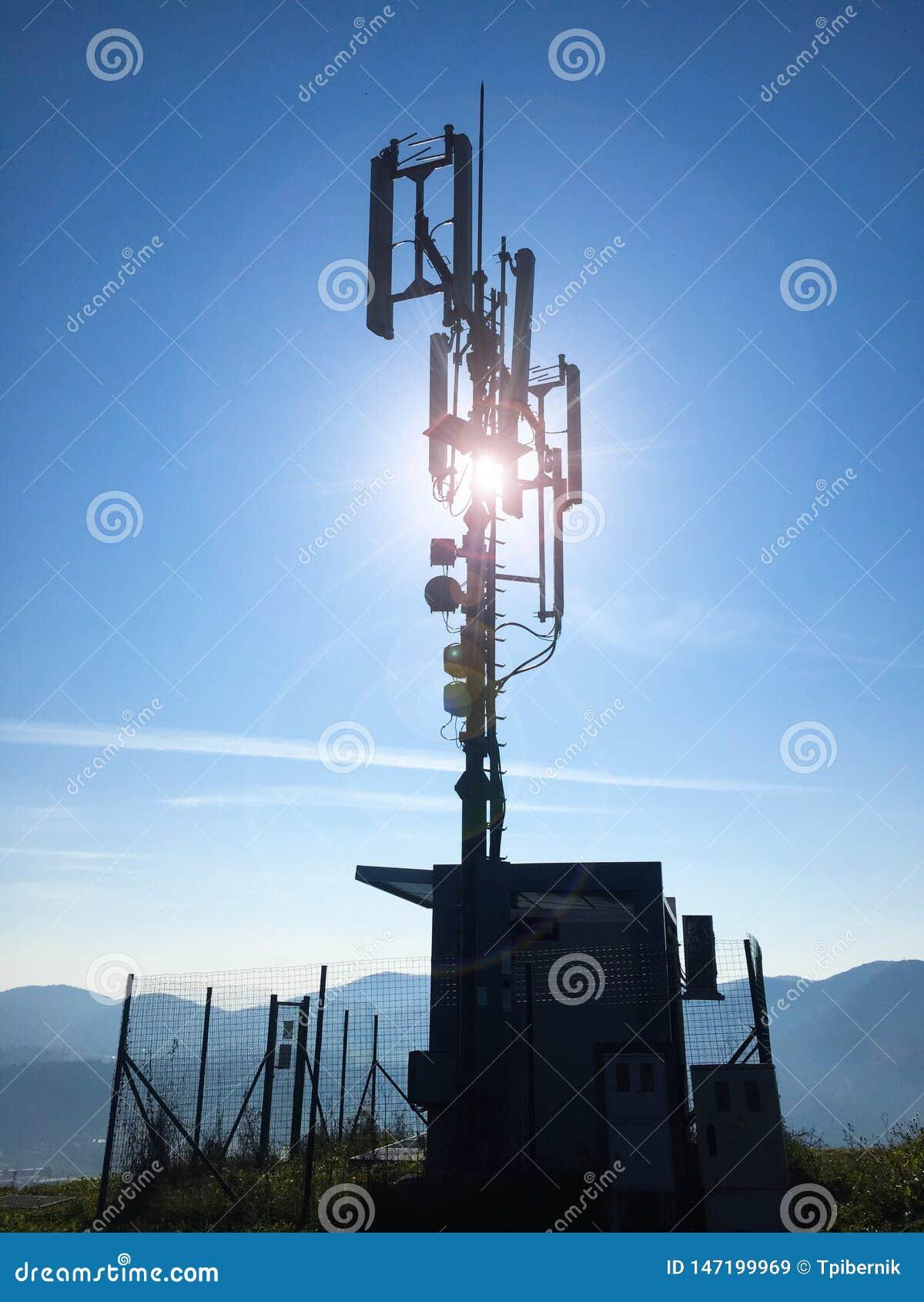 Силуэт антенн высоких клетчатых базовой станции радиосвязи на солнечный день