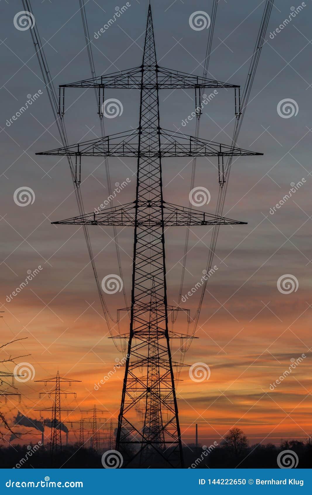 Силуэт высоковольтных линий электропередач против неба захода солнца