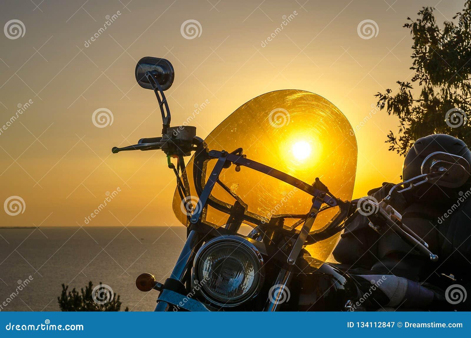 Силуэт женщины велосипедиста отдыхая на пляже на предпосылке захода солнца, наслаждающся свободой и активным образом жизни, имеющ
