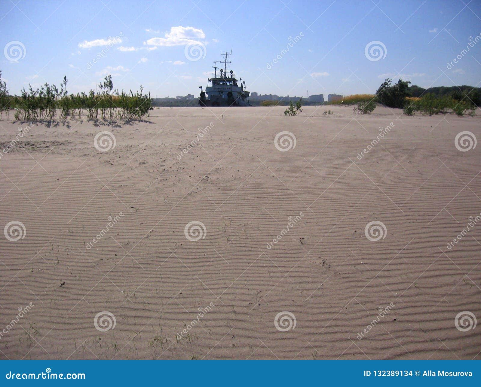 Силуэт корабля против песочной пустыни увиден в расстоянии