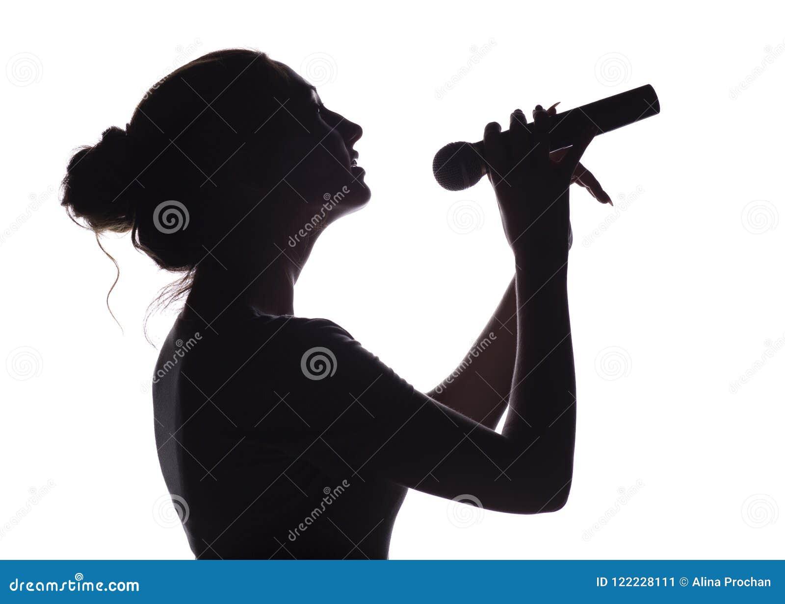 Силуэт красивой девушки поя в изолированный микрофон, профиль стороны молодой женщины выполняя лиричную песню на белизне