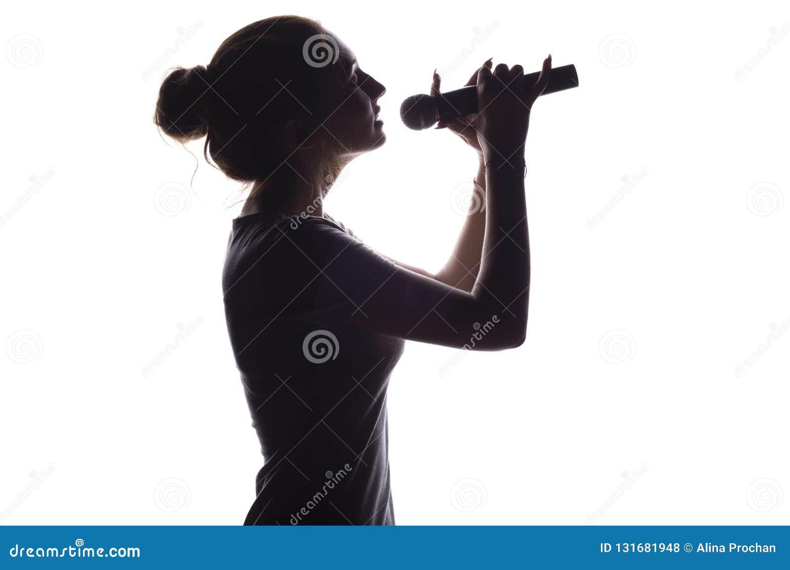 Силуэт красивой девушки с отборными волосами поя в микрофон, профиль стороны молодой женщины выполняя лиричную песню дальше