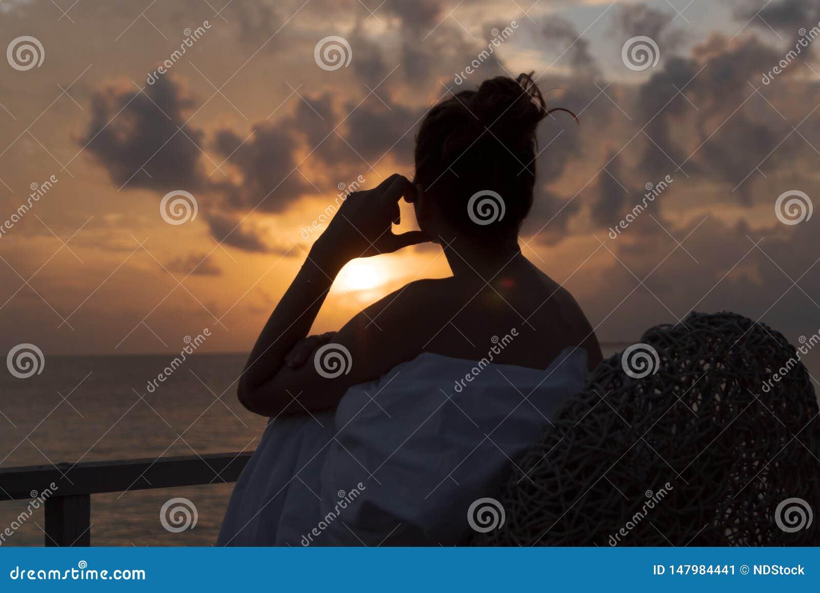 Силуэт красивой женщины предусматривая восход солнца от балкона над морем