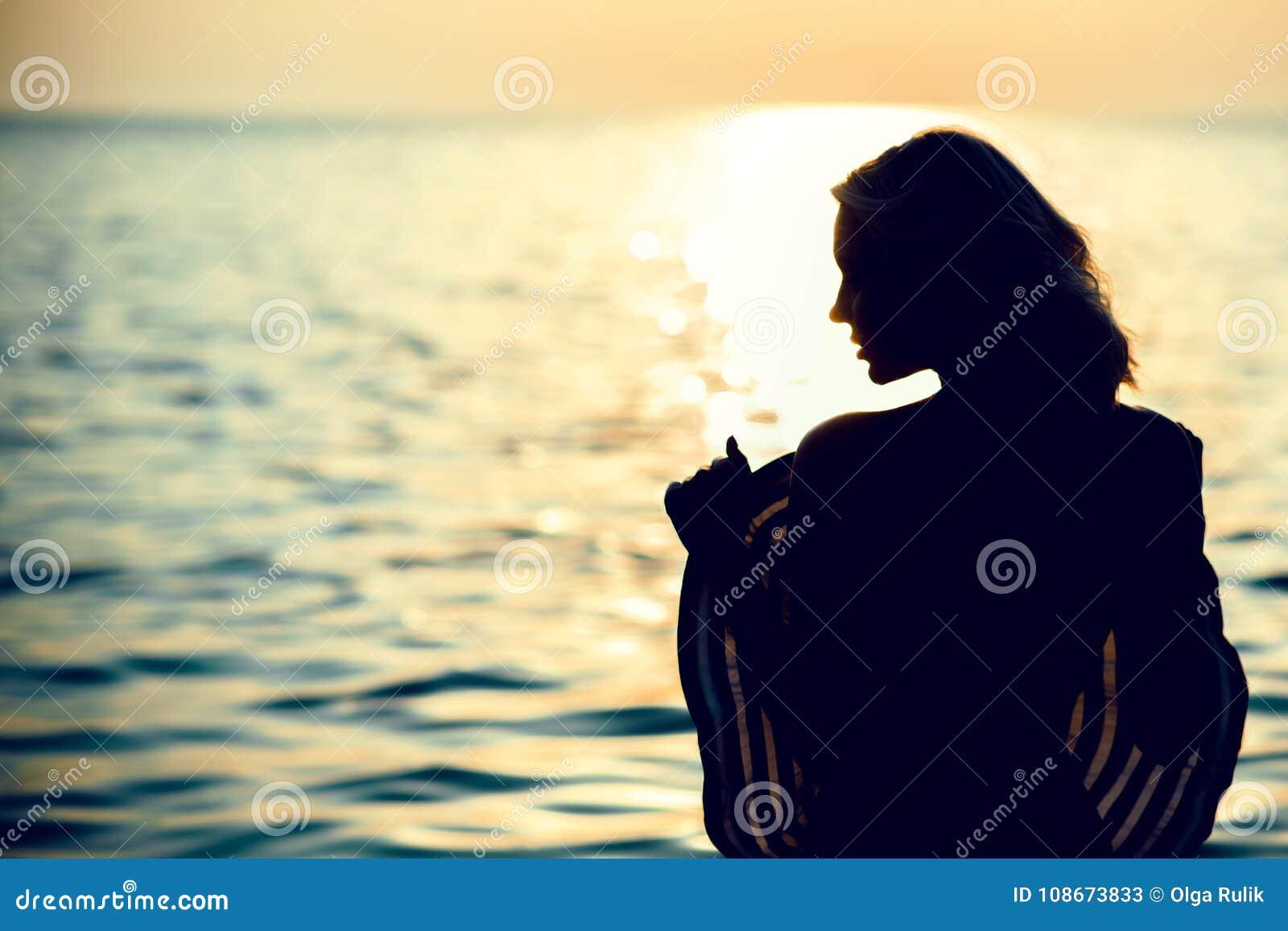 Силуэт красивой женщины стоя с ей назад к камере в морской воде на восходе солнца держа большую широк-наполненную до краев шляпу