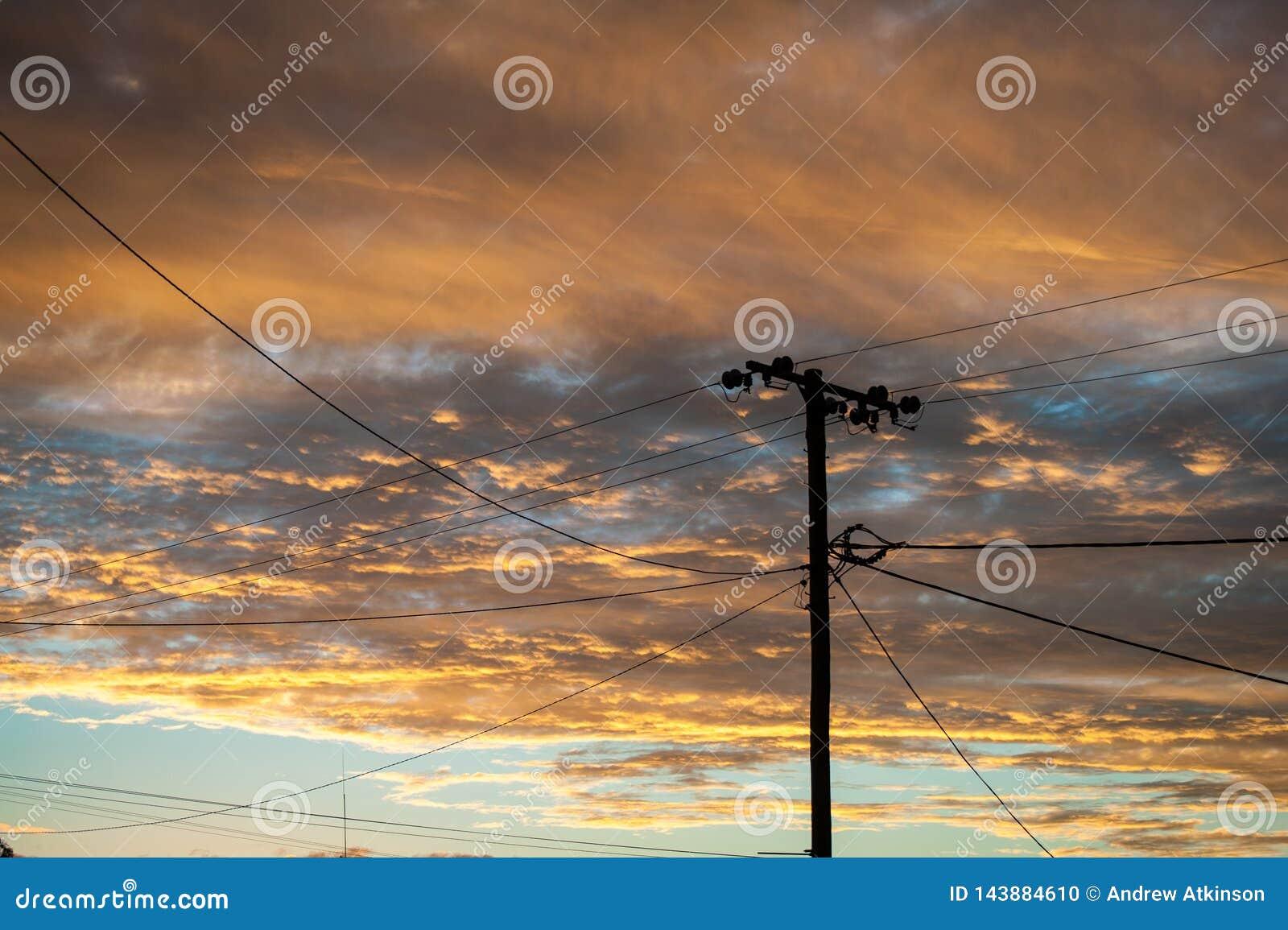 Силуэт линии электропередач в молнии Ридж назад осветил заходом солнца