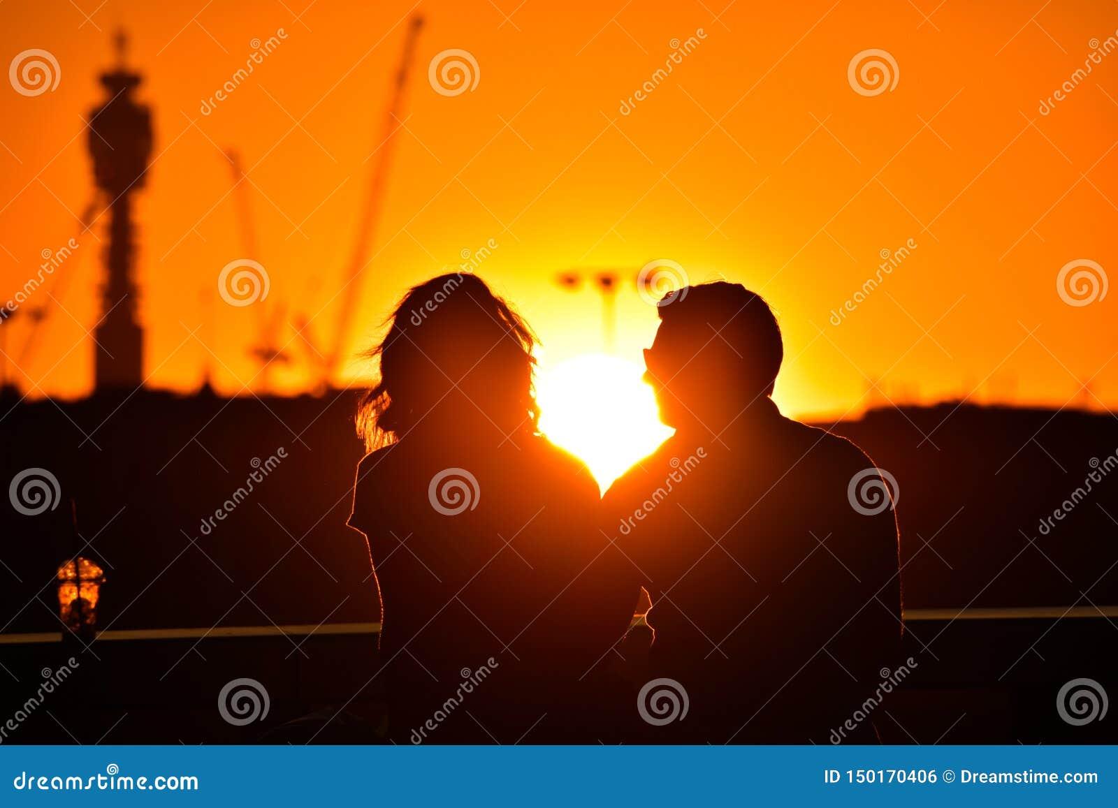 Силуэт любя пар наблюдая красивый яркий романтичный заход солнца