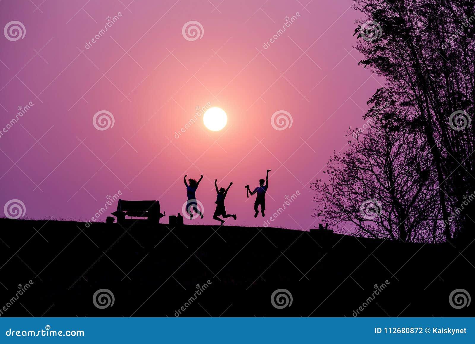 Силуэт людей скача против под захода солнца