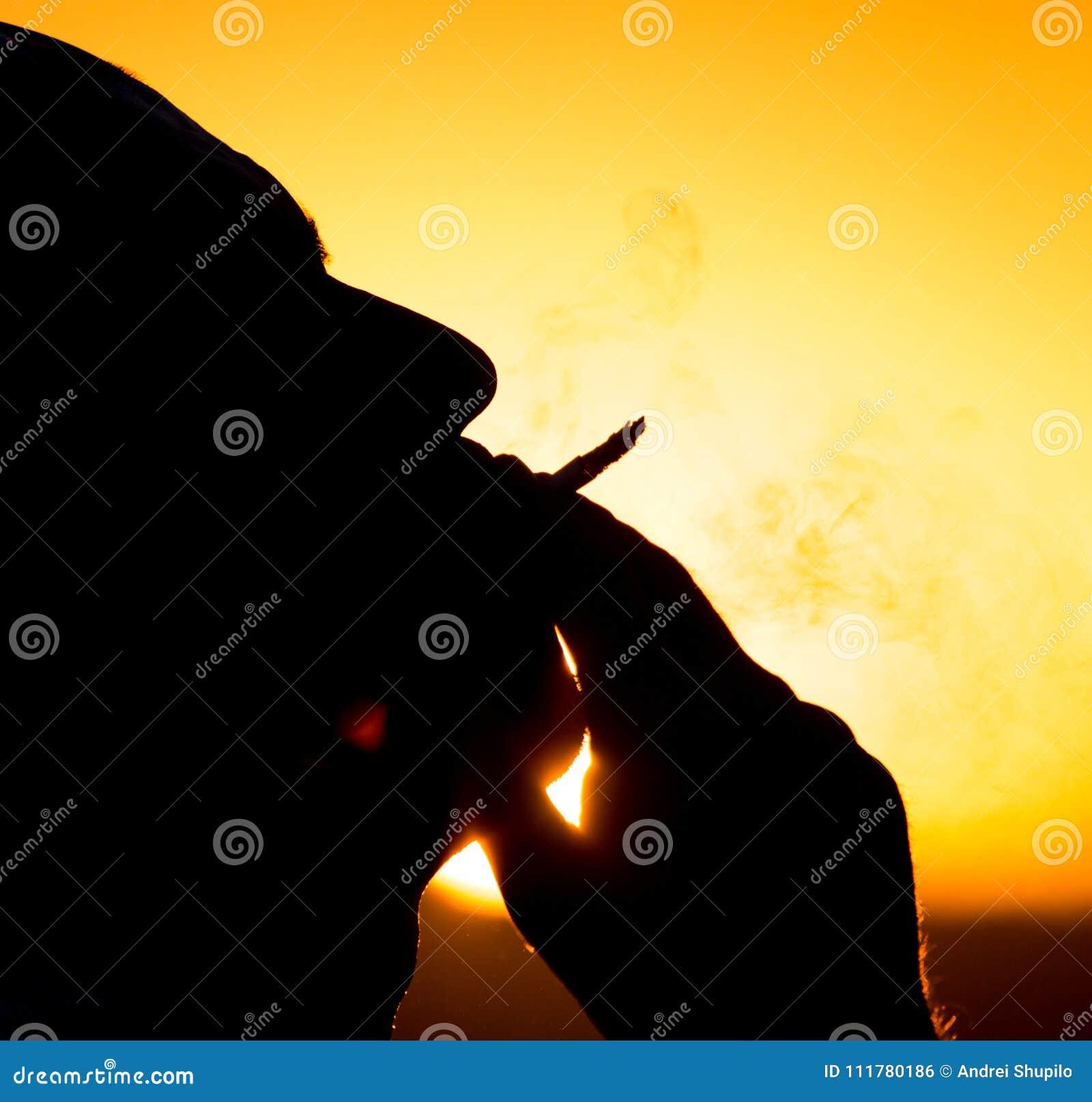 Силуэт мужских курильщиков в заходе солнца
