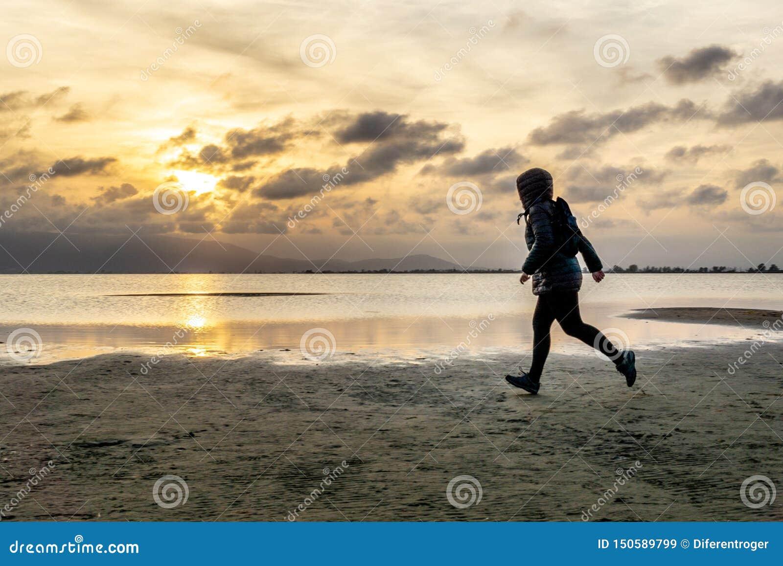Силуэт непознаваемой женщины идя на пляж на заходе солнца